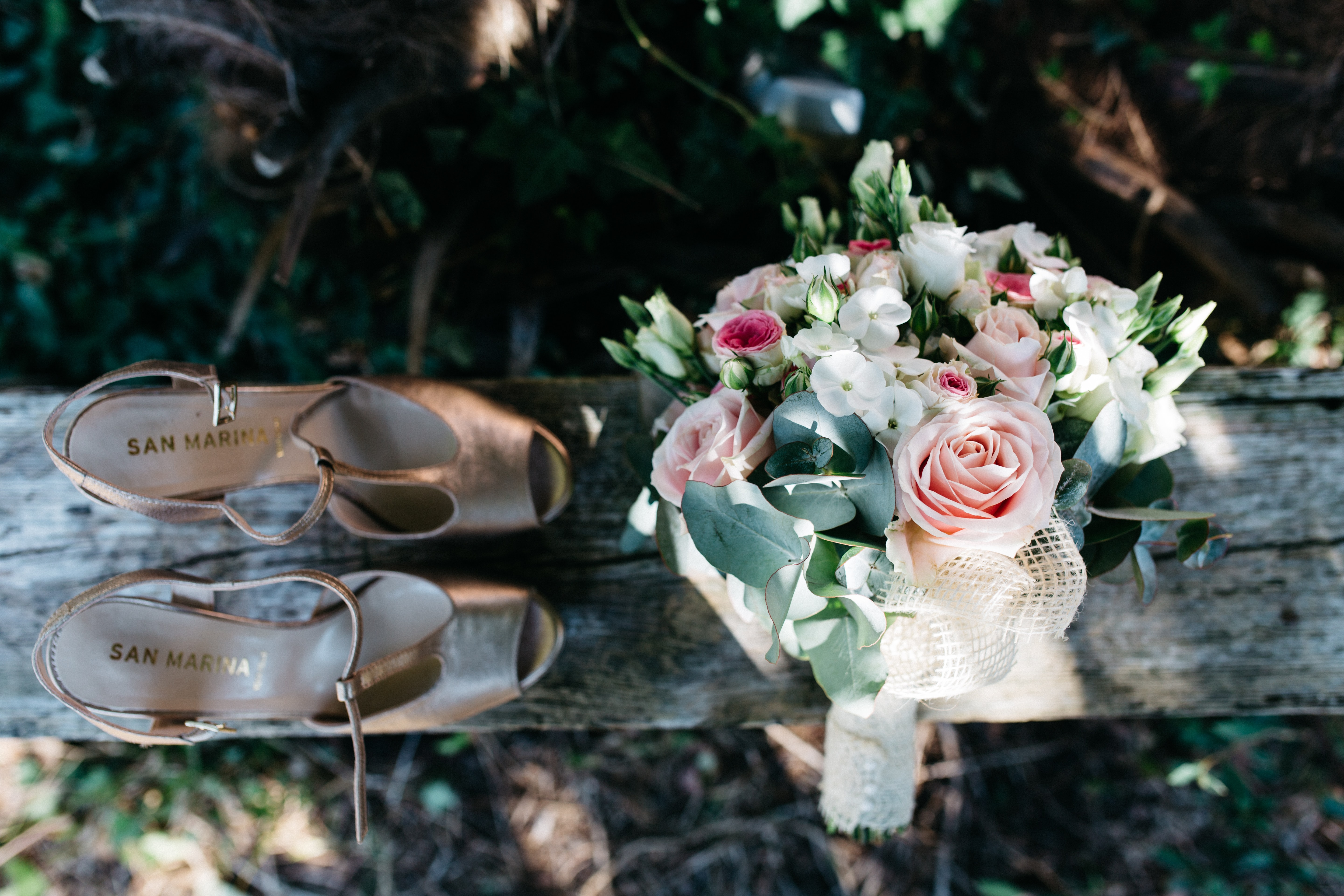 A pair of woman's shoes next to a magnificent flower bouquet on a wooden bench