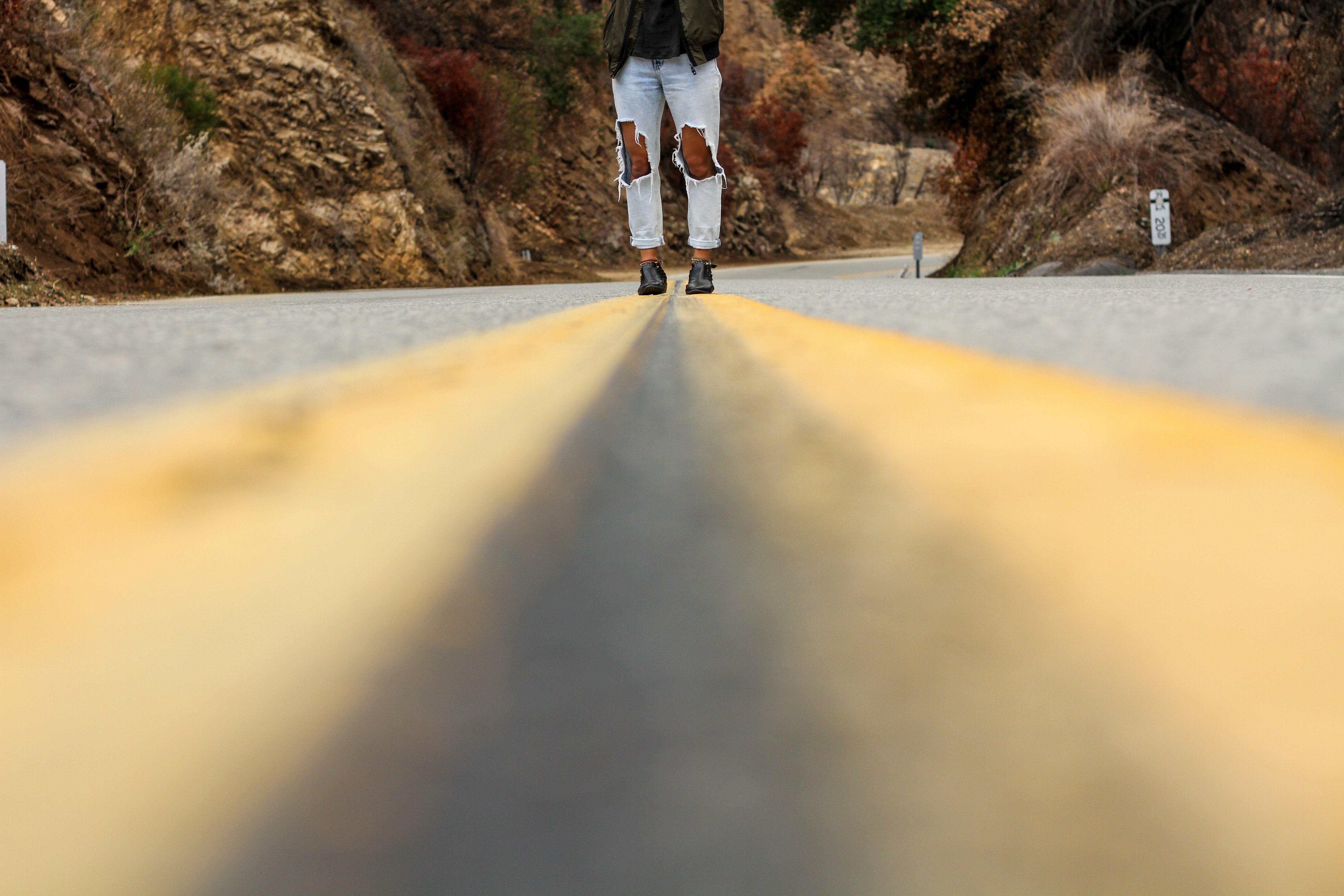 A person in ripped jeans standing in the middle of an empty road through a canyon