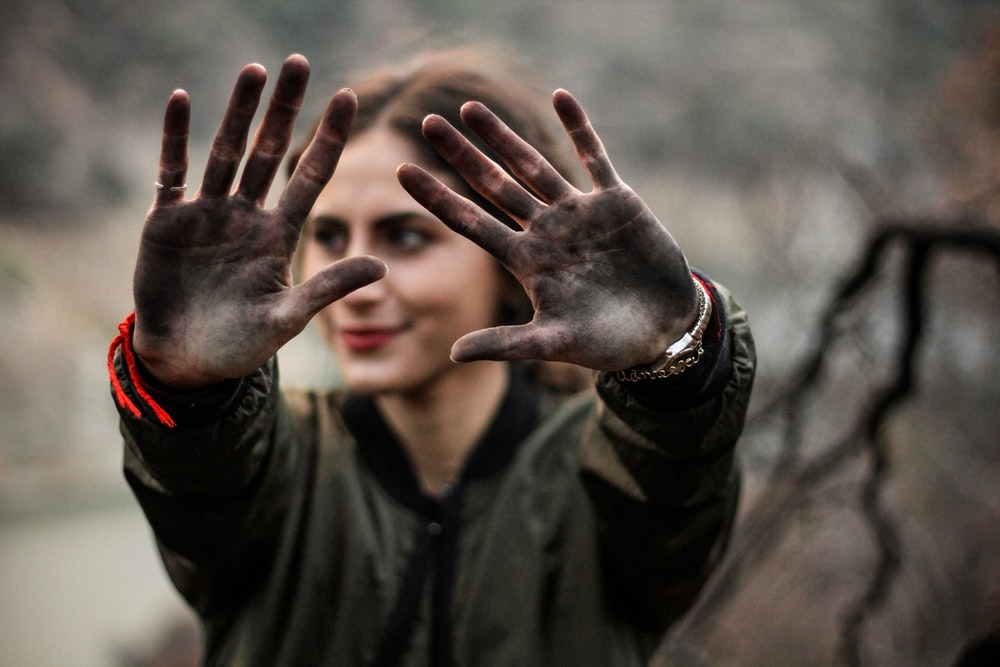 woman showing her hands with black paint