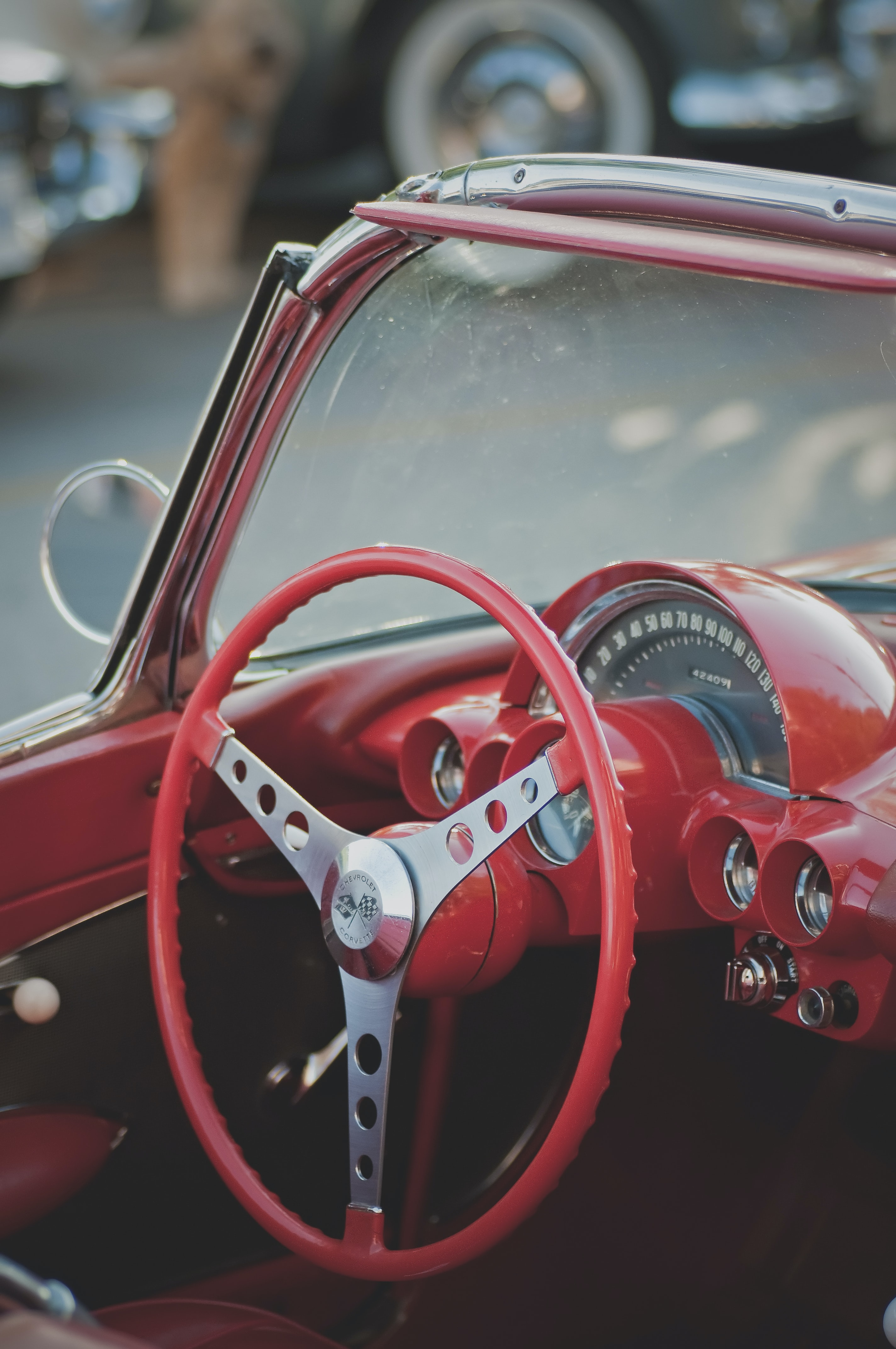 A red steering wheel inside a convertible with red interior.