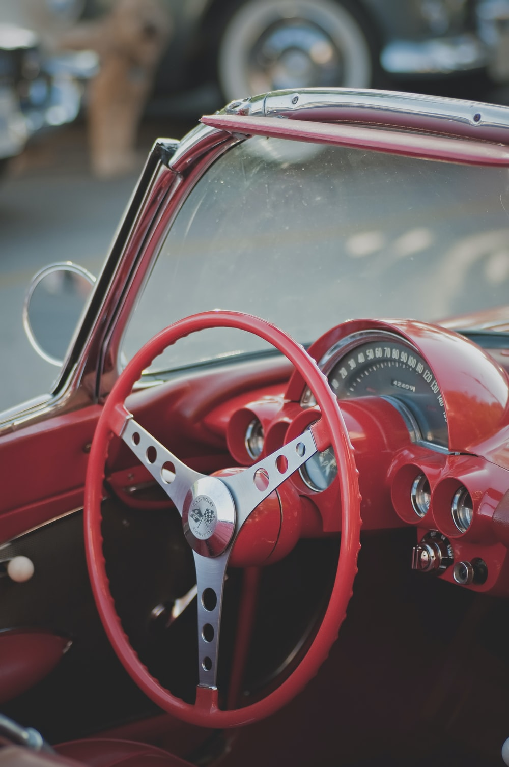 red vehicle steering wheel in closeup photo