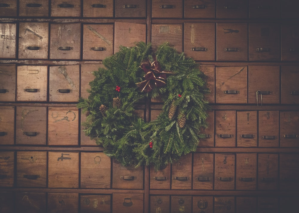 green and brown pinecone Christmas wreath on wooden drawers