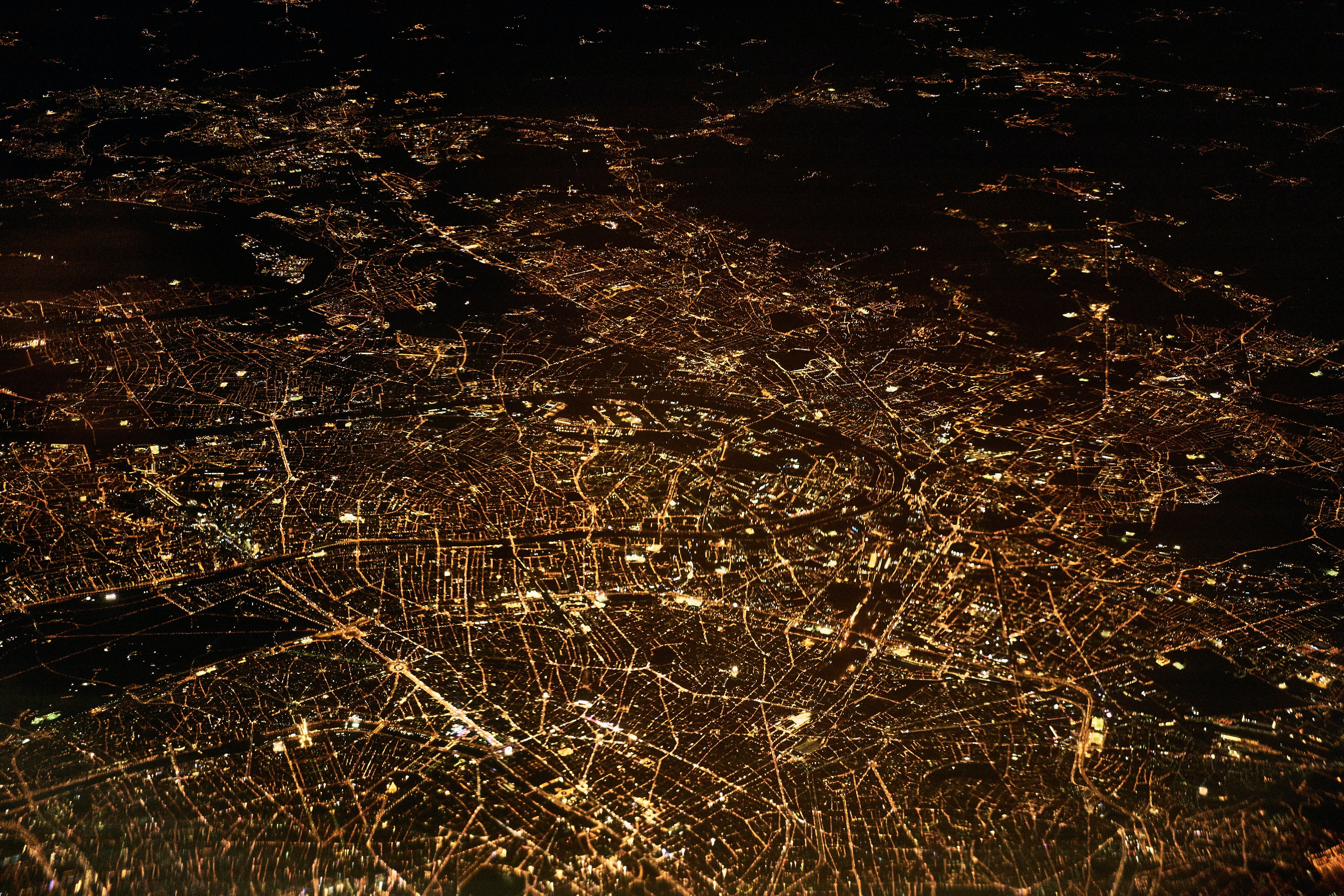 The cityscape of Paris all lit up at nighttime from a plane window