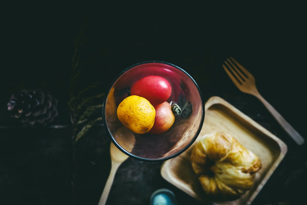apple and orange fruits in bowl beside plate and fork