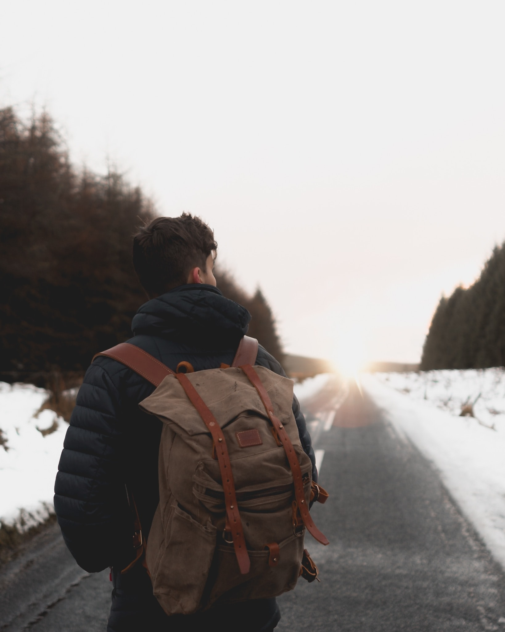 A guy walks with a backpack on a road during the winter in Springwell Forest, United Kingdom