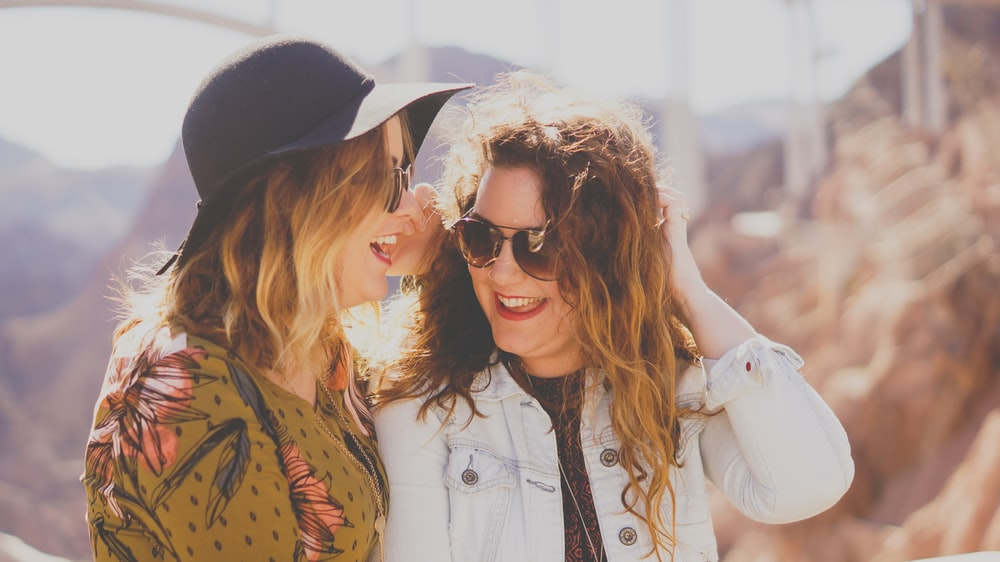 two women smiling while wearing sunglasses