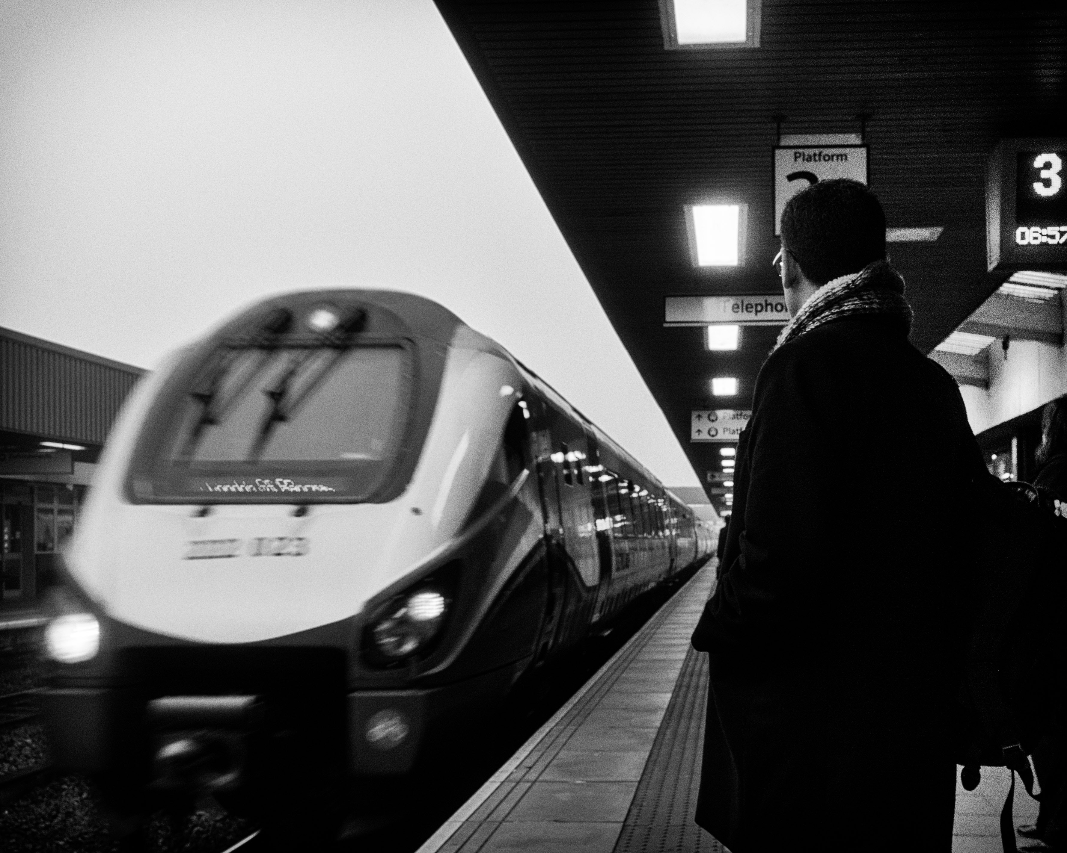 Black and white behind  shot of man in coat with scarf standing on Leicester train platform
