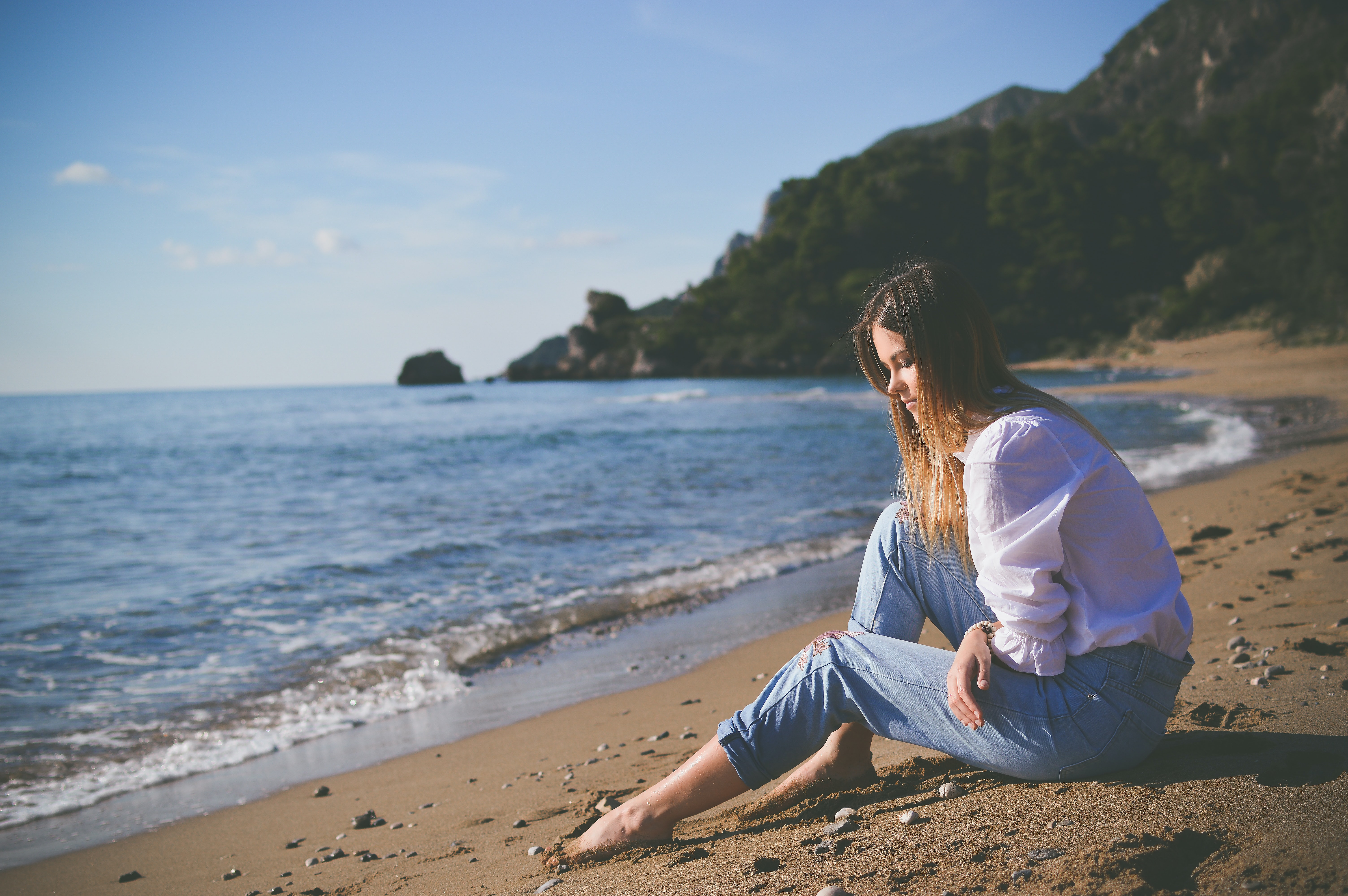 woman sitting on beach shore during daytime