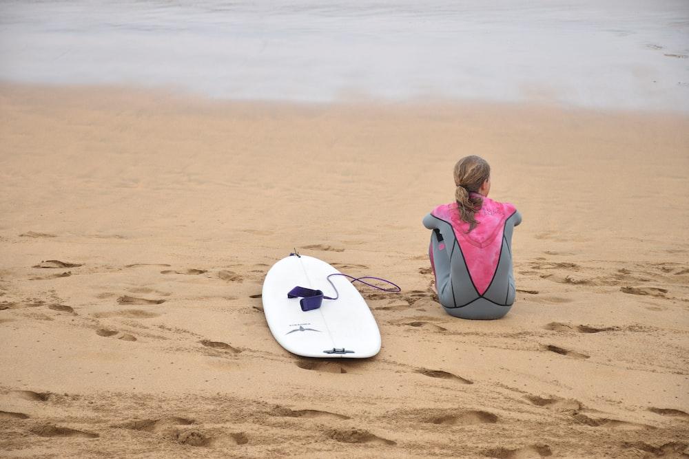 woman sitting on shore beside surfboard near sea