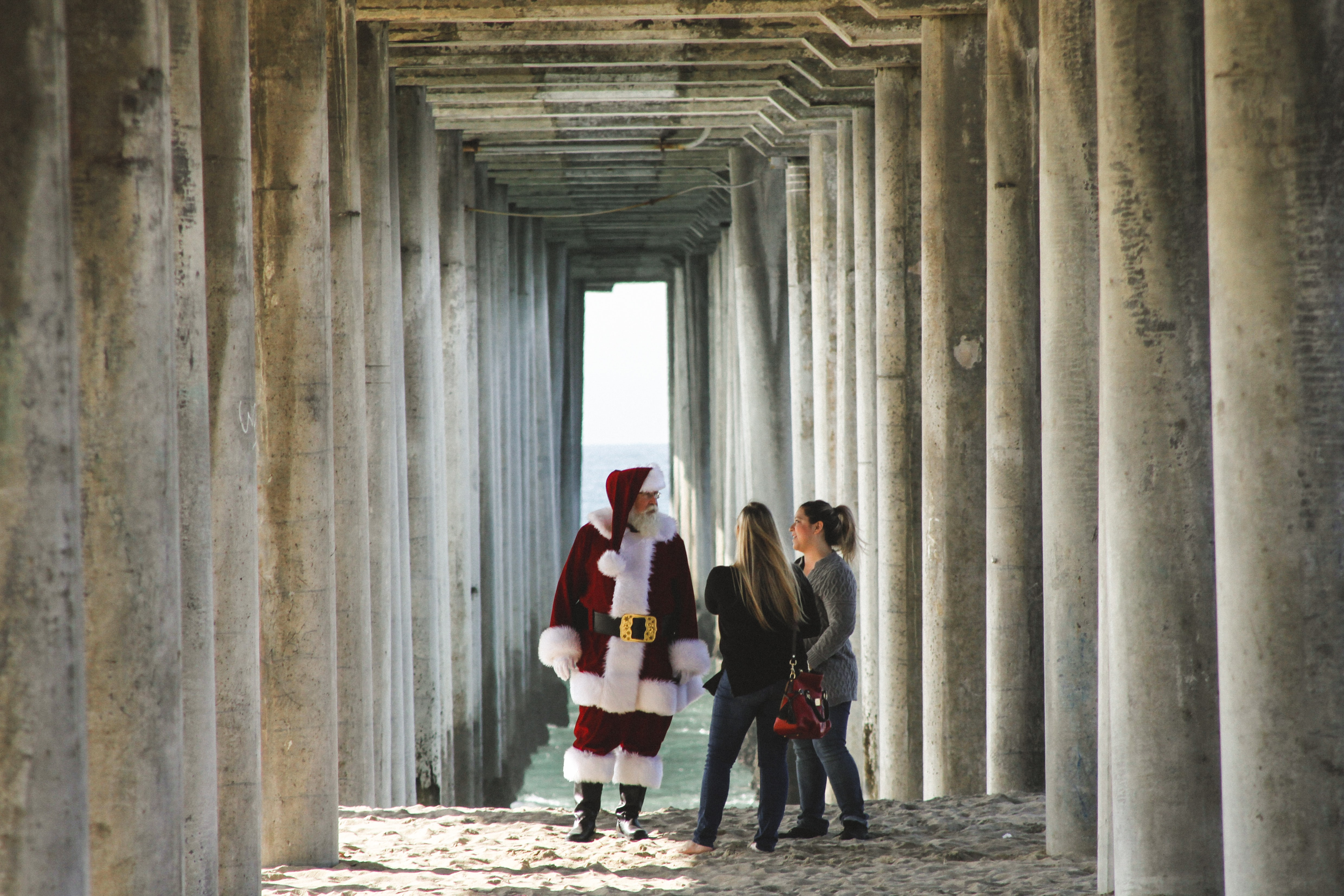 Santa Clause talking to two women under the pier at Huntington Beach