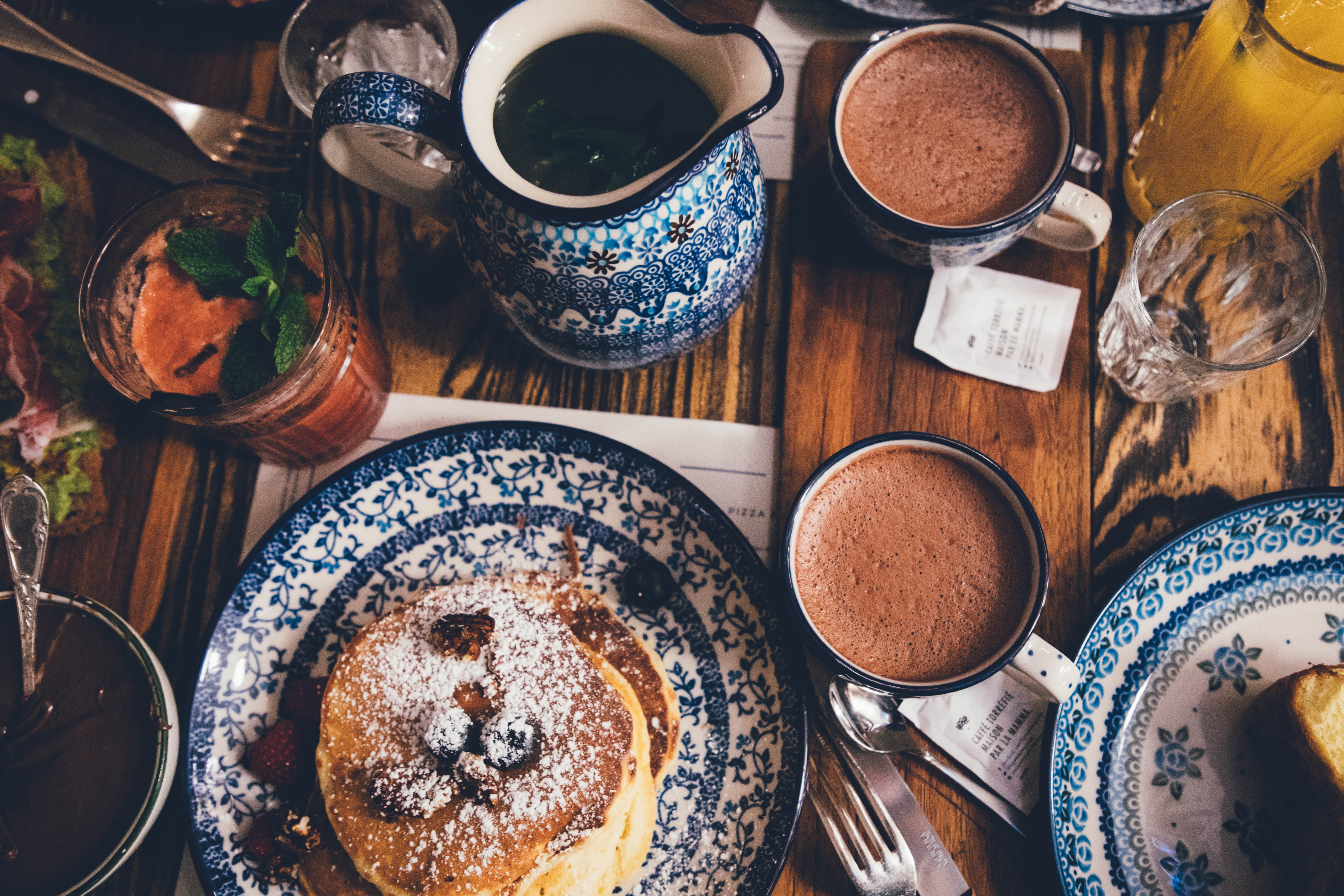 An overhead shot of a breakfast table with pancakes, mugs, drinks, and food