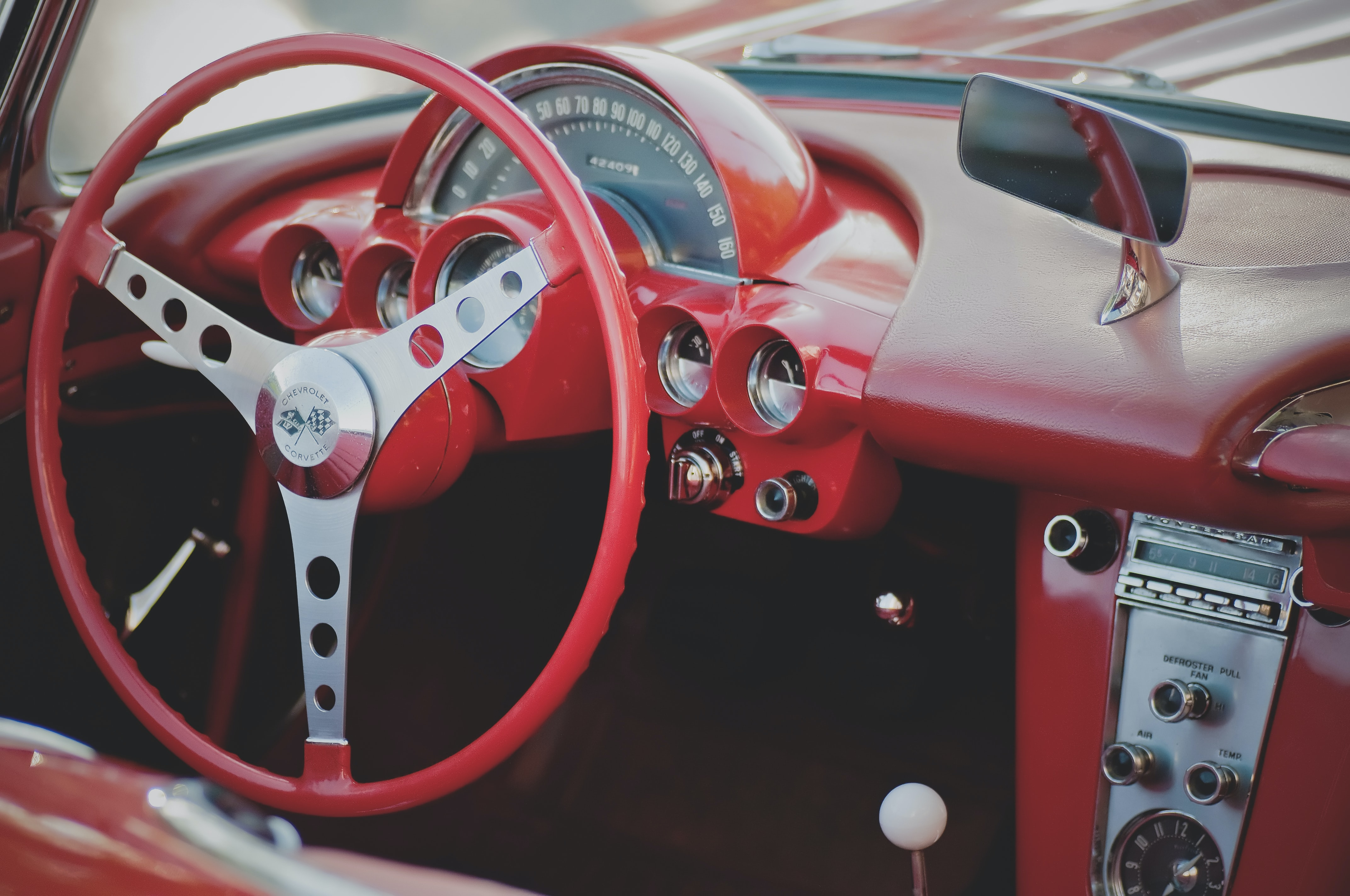 Red interior of vintage Chevrolet car with steering wheel and dashboard