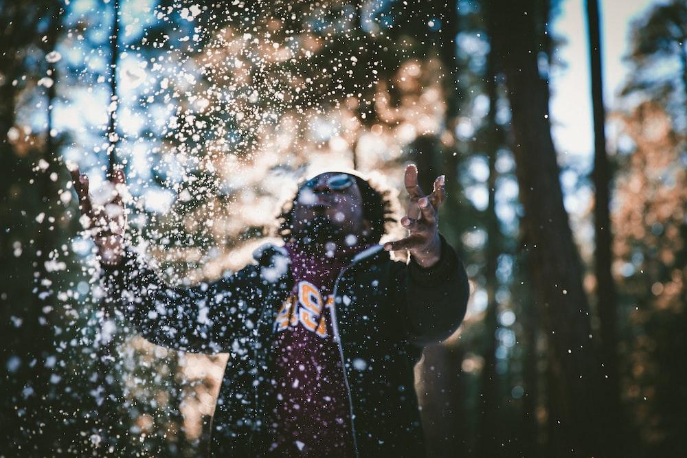 man playing water drops during daytime