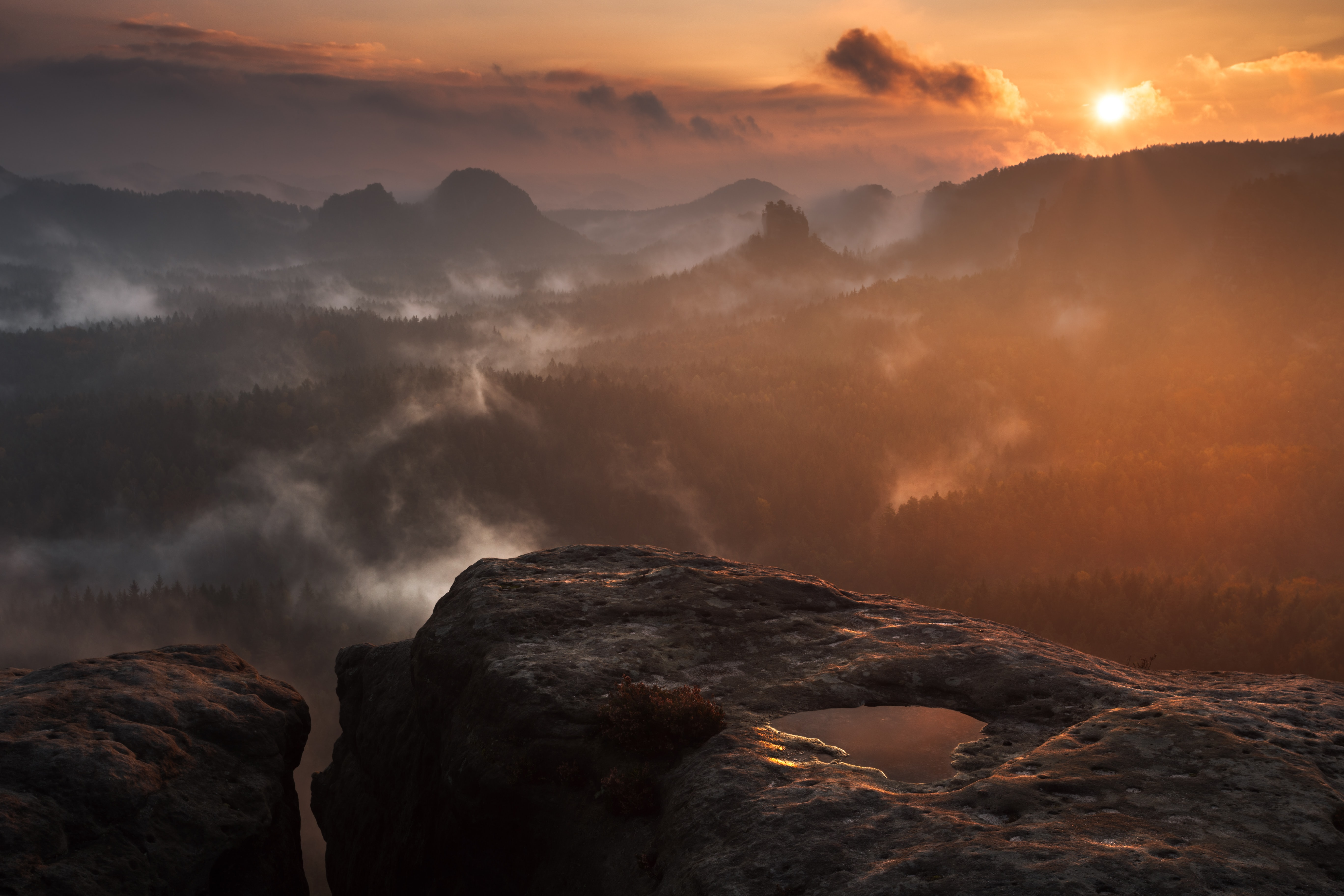 A puddle on a smooth rocky ledge overlooking foggy forests during sunset