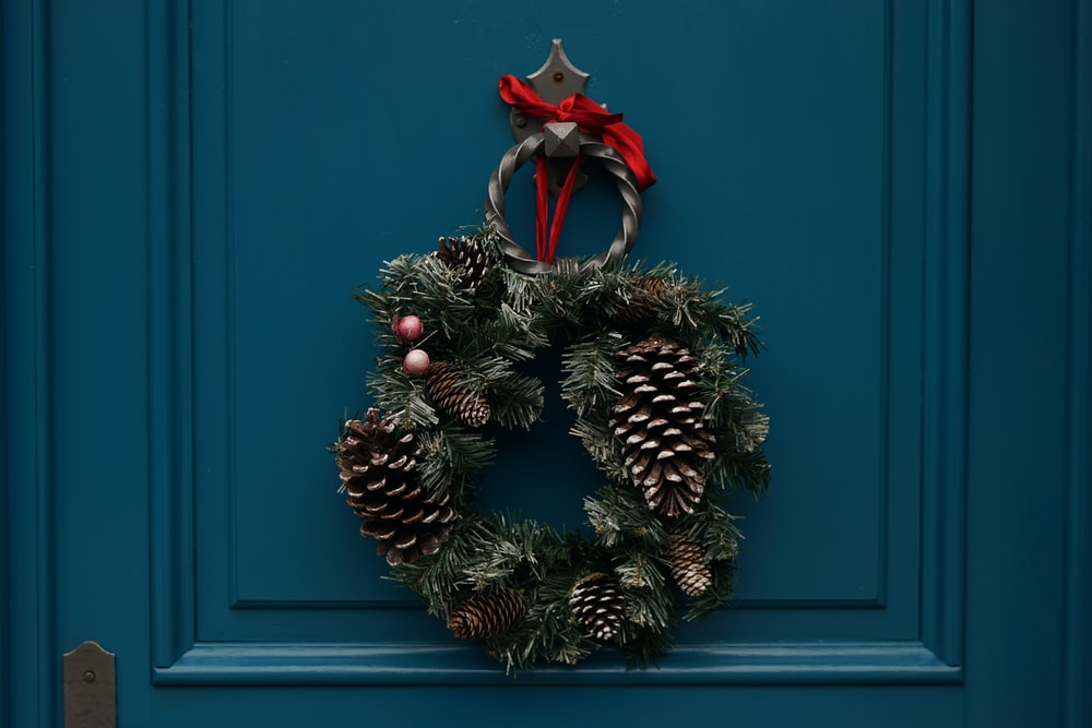 An evergreen wreath decorated with berries and pine cones hangs on a teal door