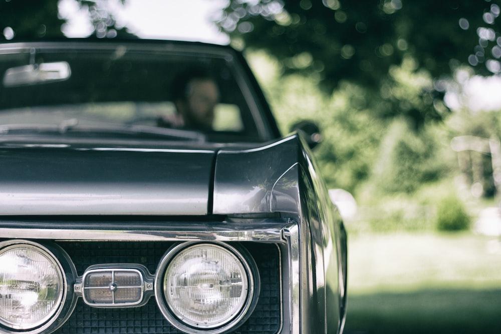 man inside black muscle car