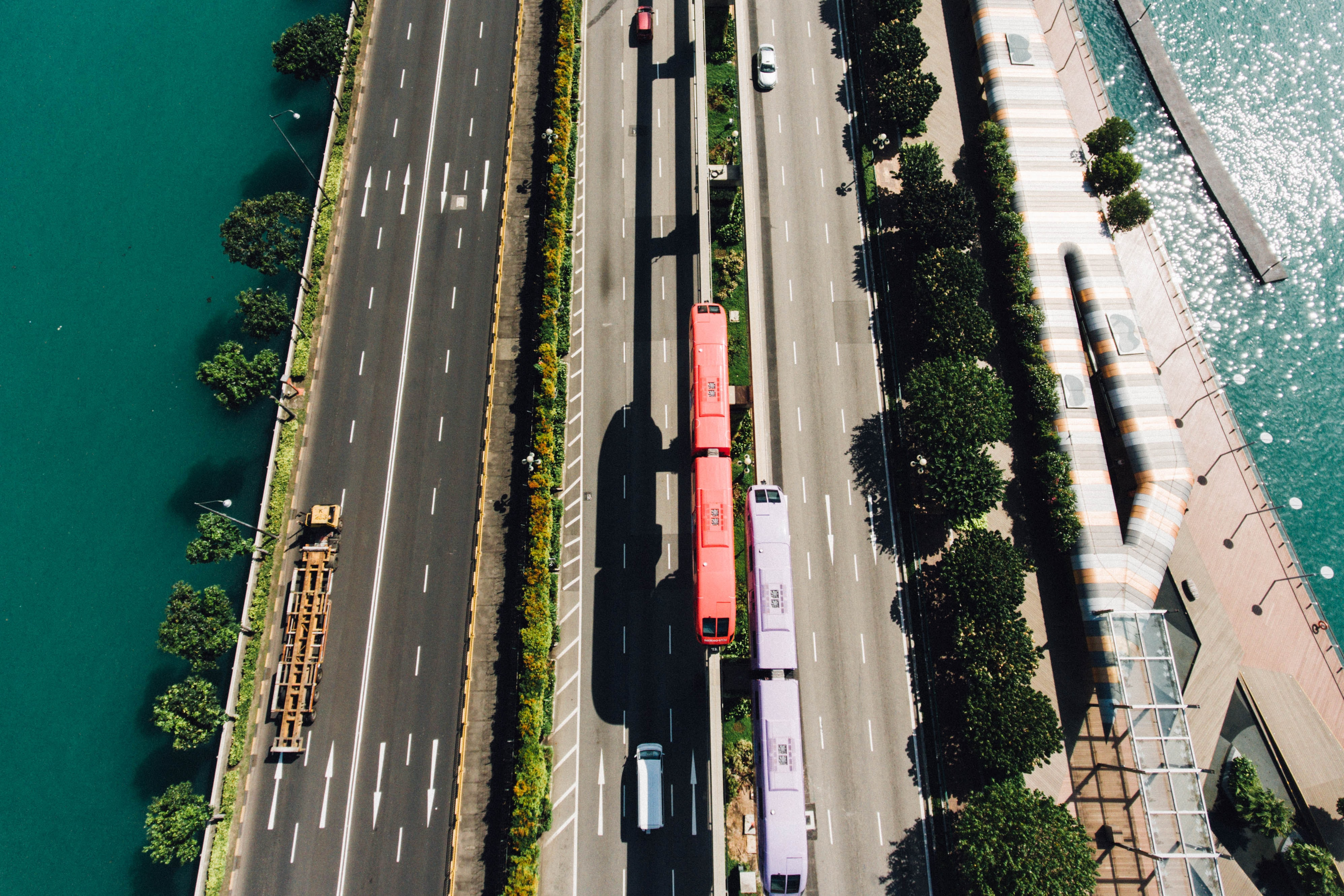 A drone shot of urban trains in the middle of a freeway in singapore