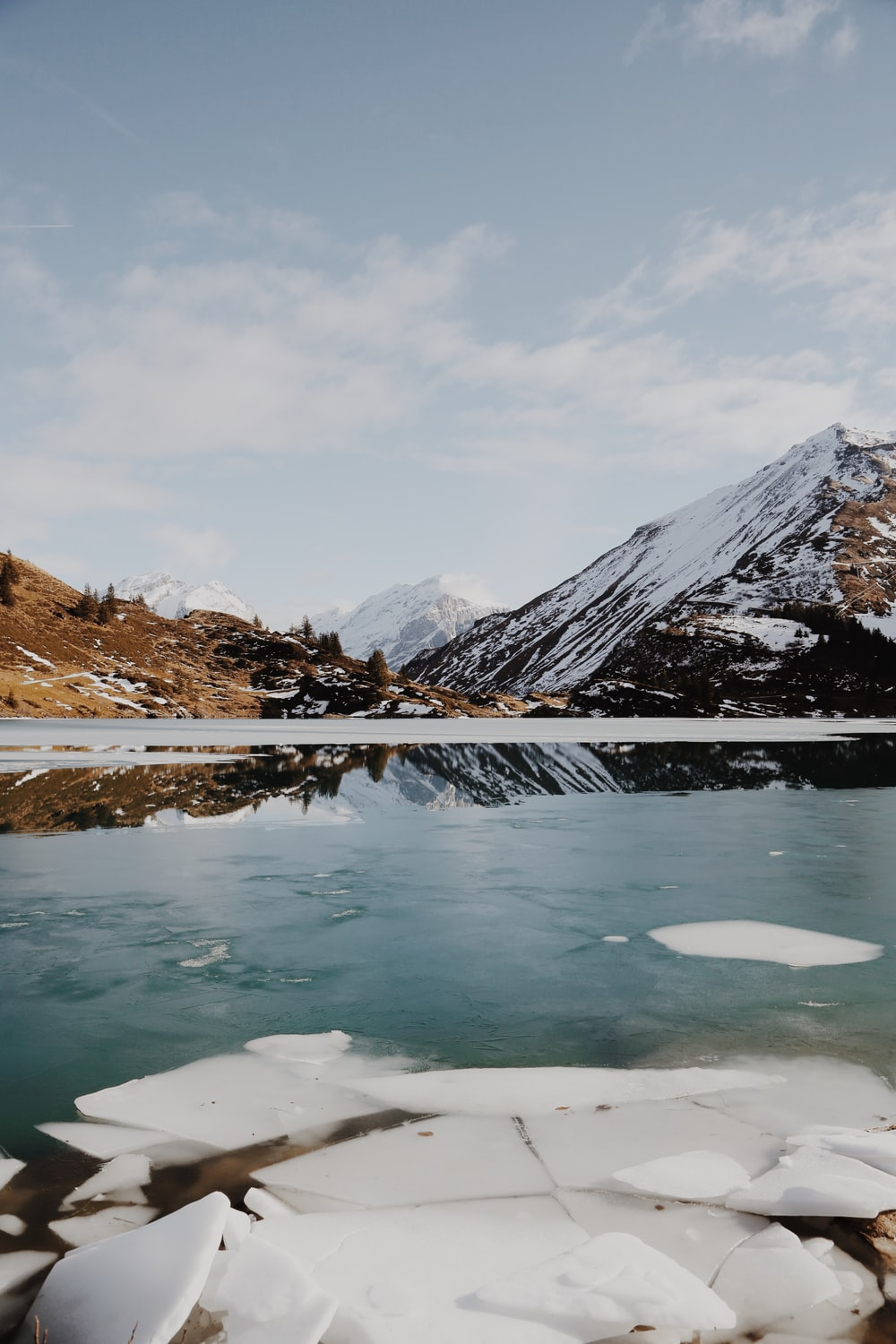 body of water beside mountain covered with snow