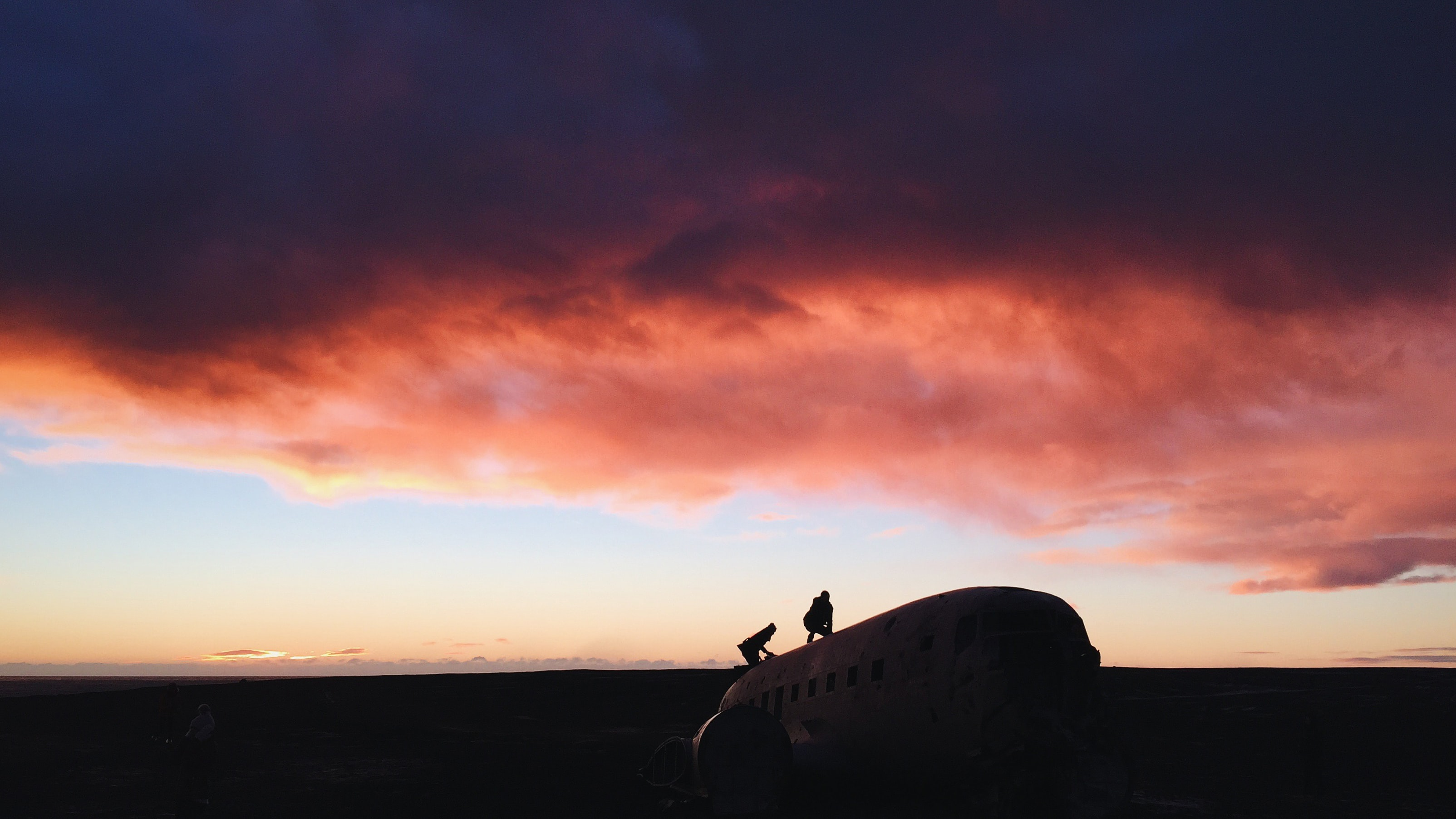 Two people climbing on an abandoned airplane under a sunset sky with pink clouds in Solheimasandur
