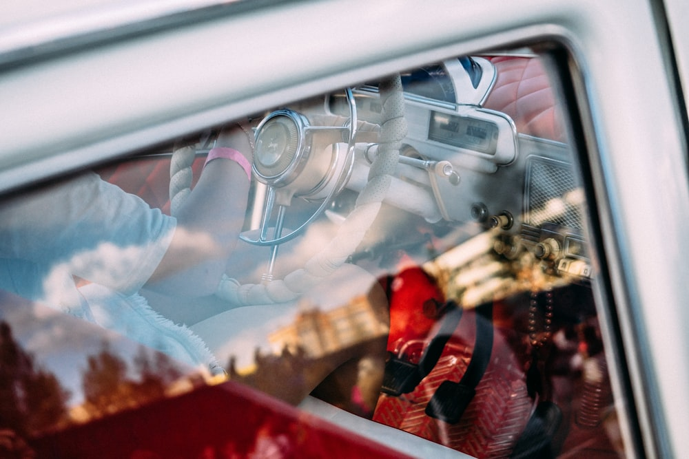 Partial view of a driver in a vintage car through the rear right window, overlapping with the reflection on the glass.