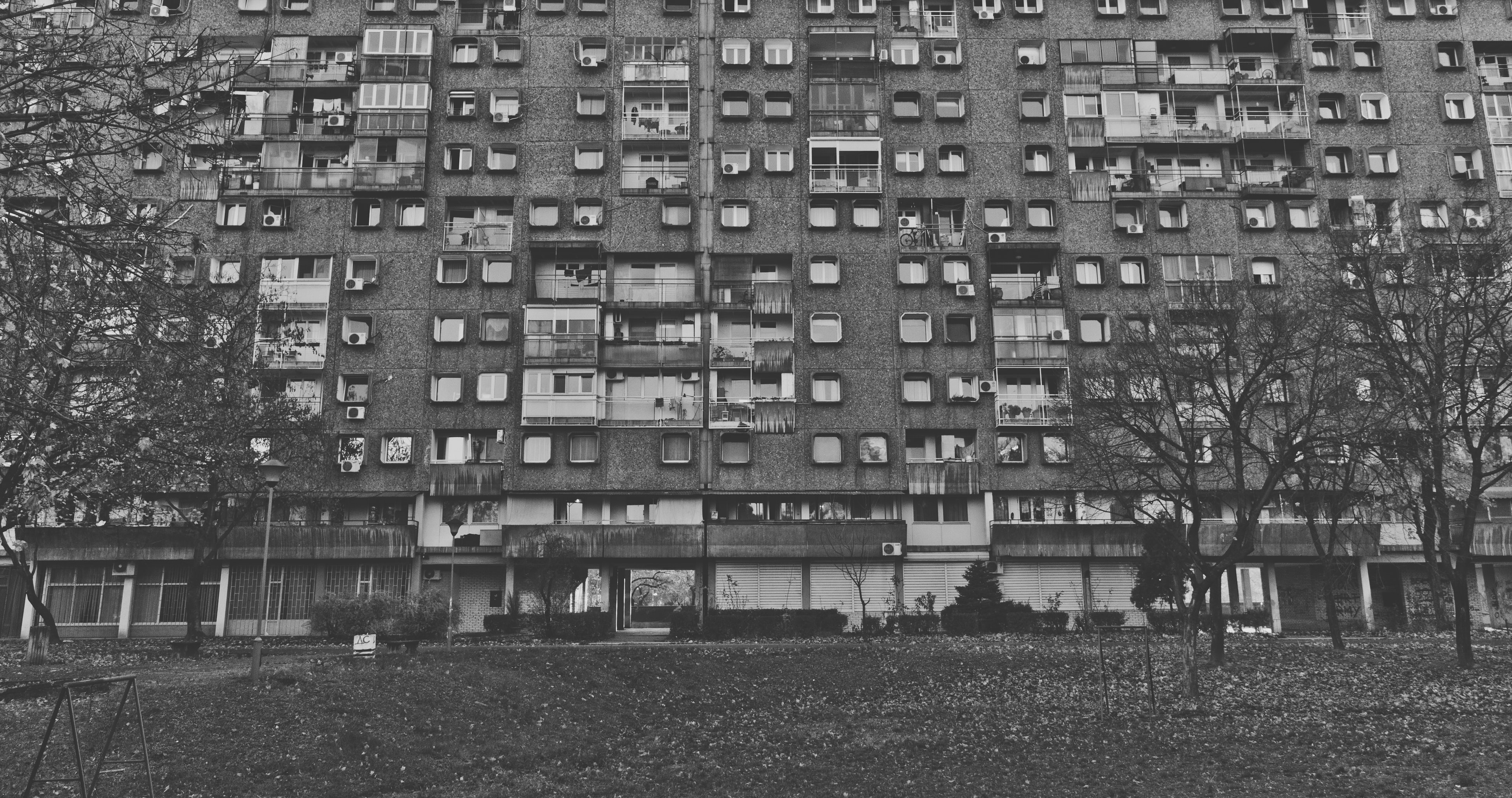 Black and white shot of rundown residential building with grass and trees in Novi Beograd