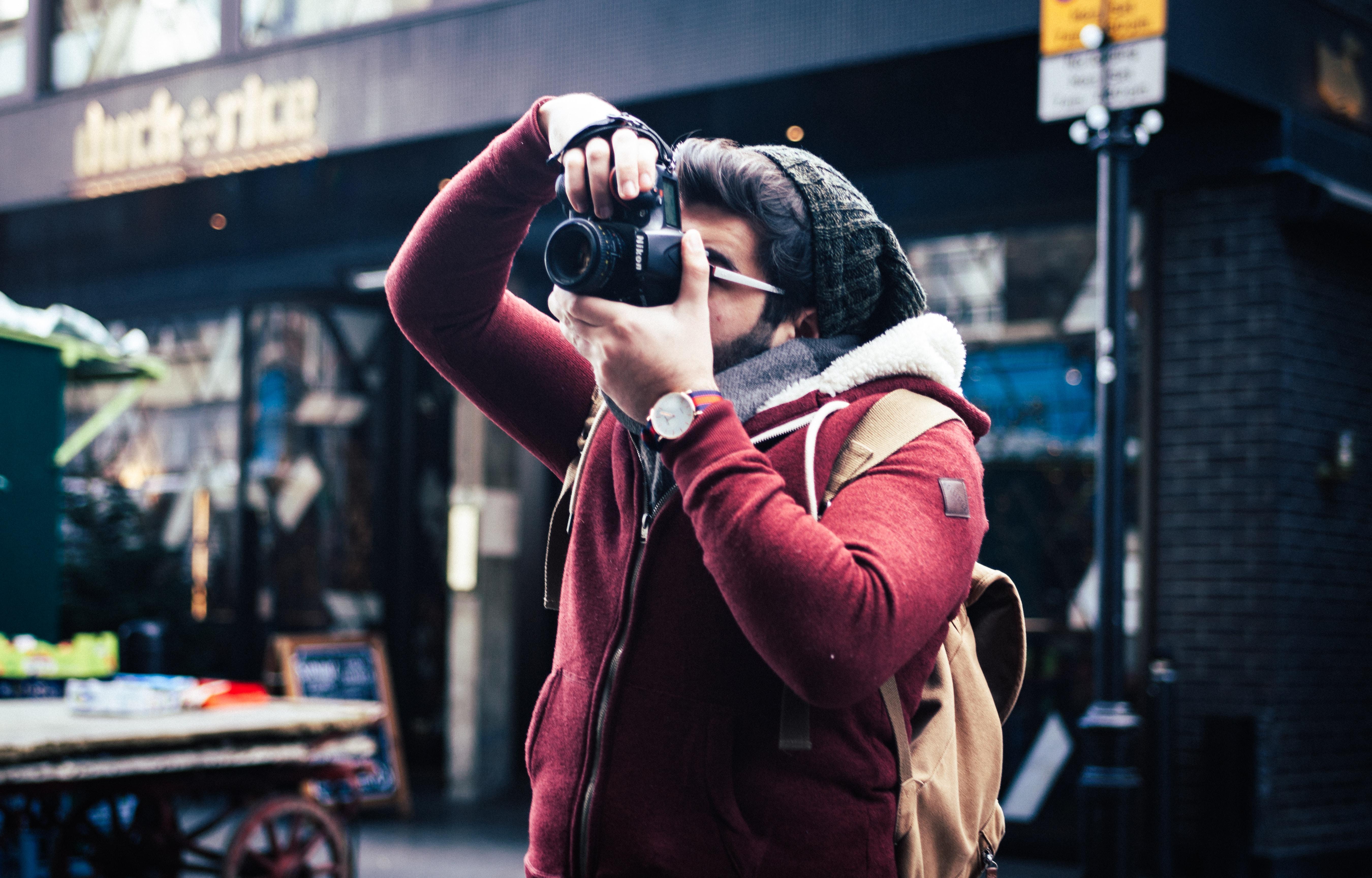 man taking a photo near storefront