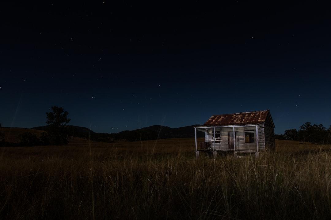 Серый и коричневый деревянный дом, окруженный травой возле горы