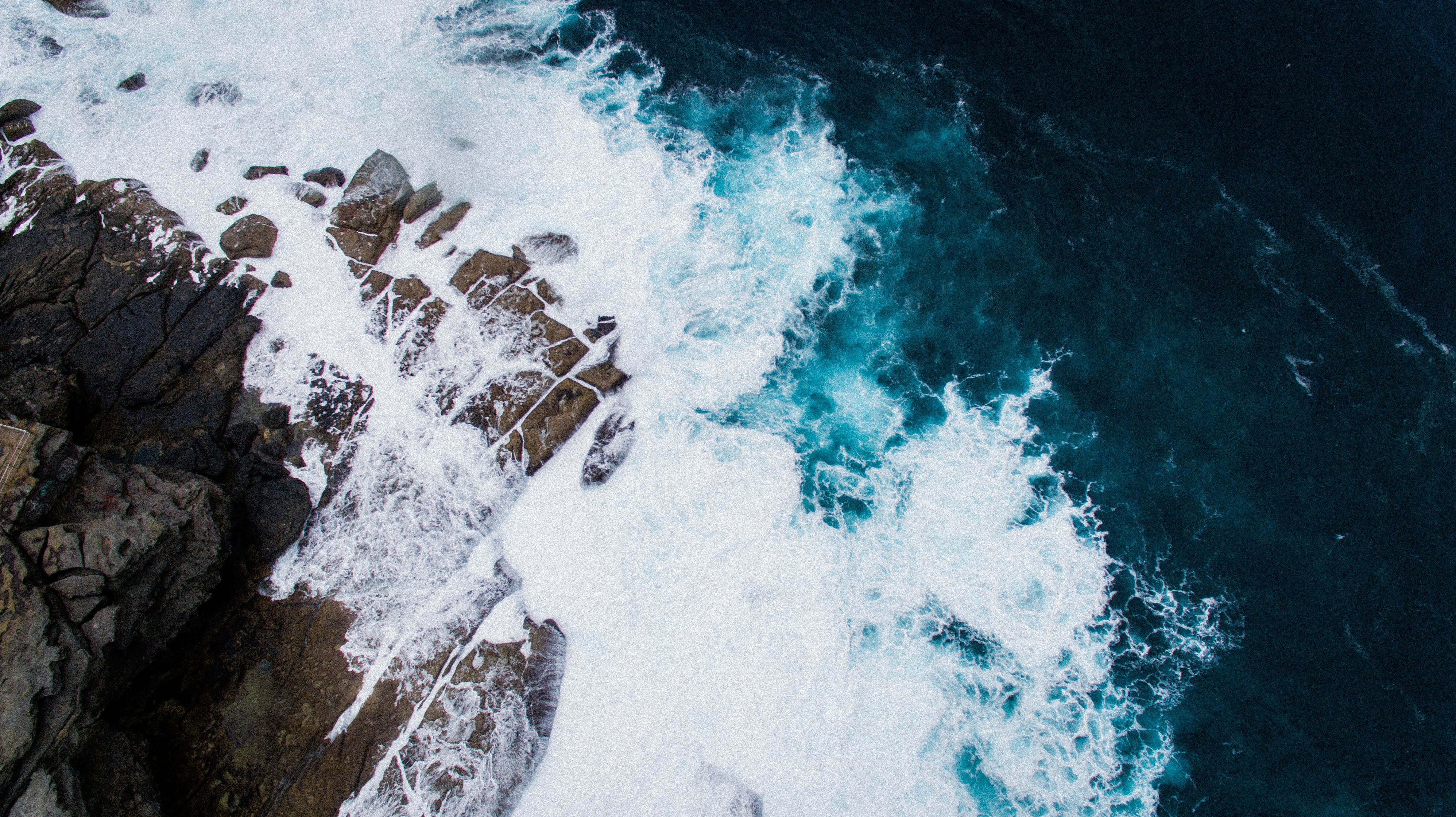 Drone aerial view of the ocean crashing on a rocky Bondi Beach