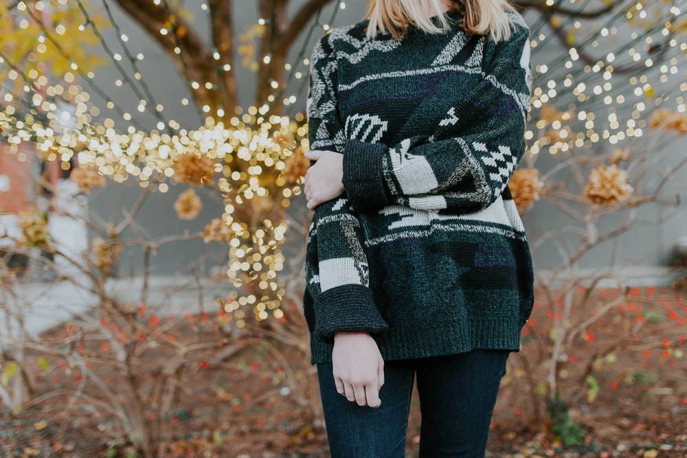 A woman wearing a cozy knit sweater standing in front of fairy lights and trees