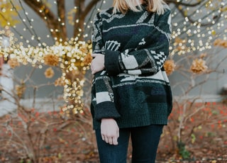 woman wearing sweater standing in front of plants and tree