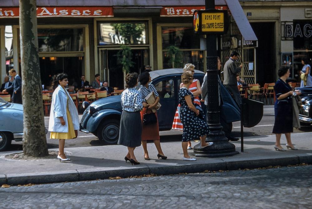 female women standing near black pole