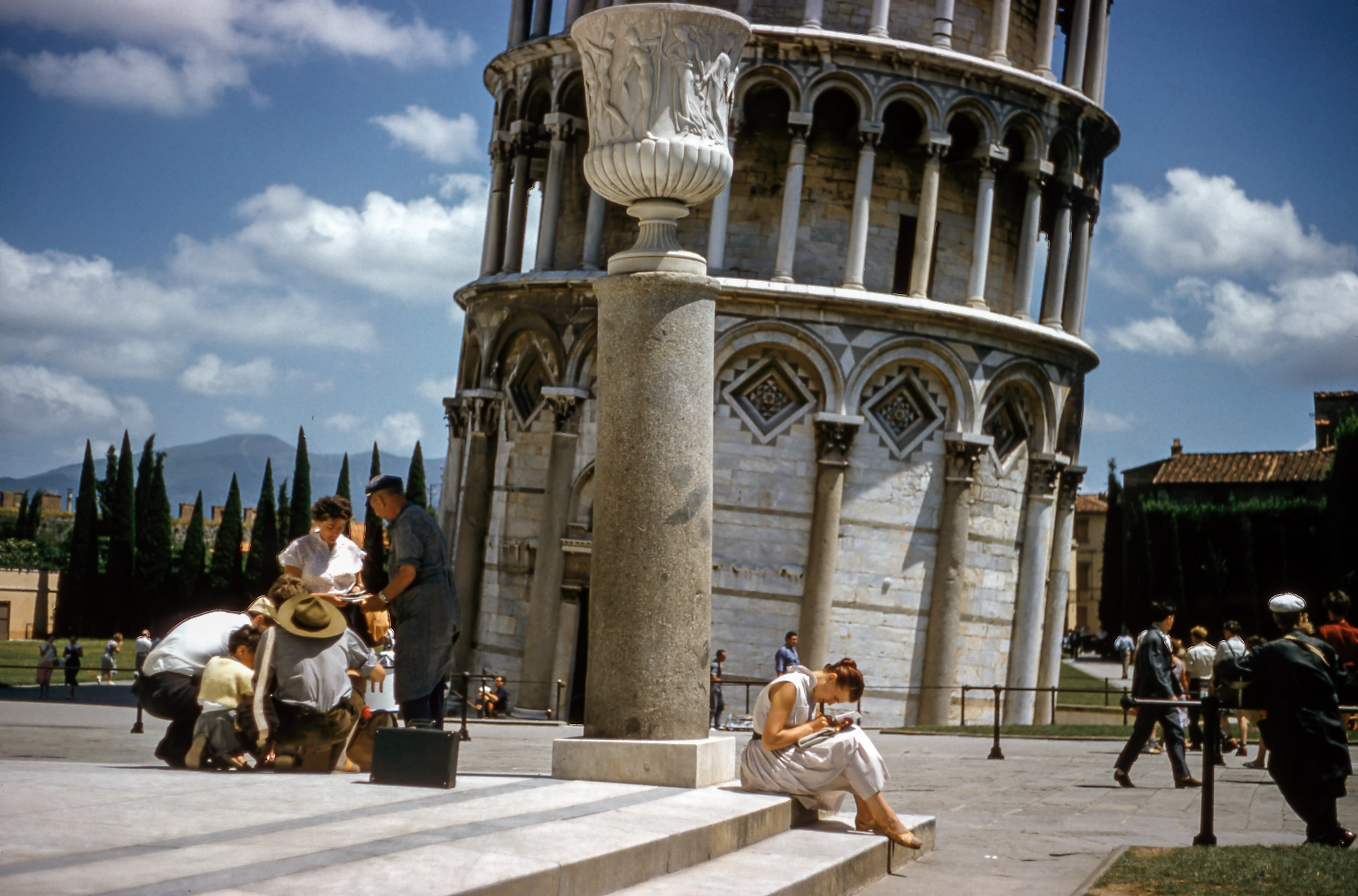 Tourists sitting and walking around the Leaning Tower of Pisa