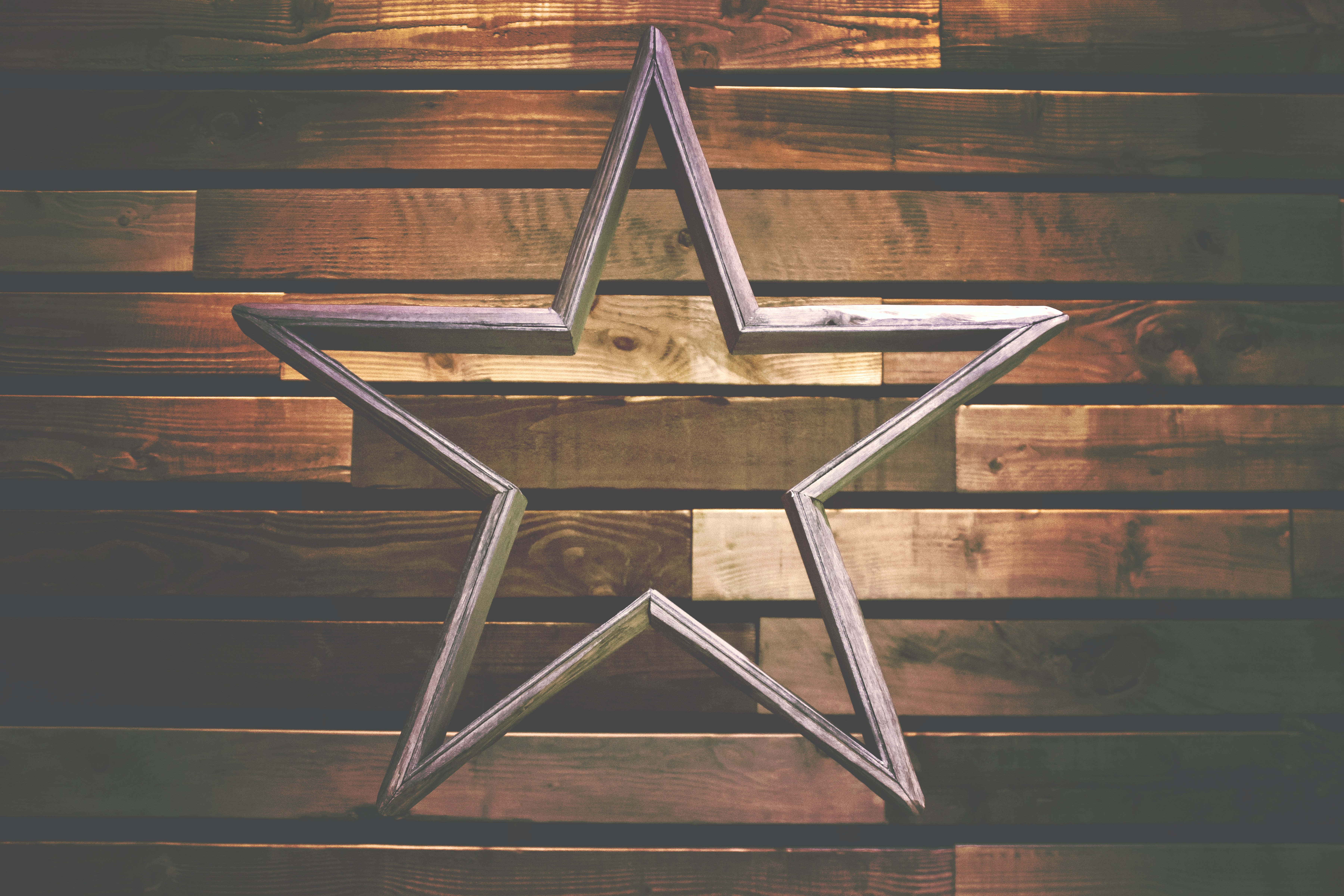 A wooden decoration in the shape of a hollow star against a wooden wall