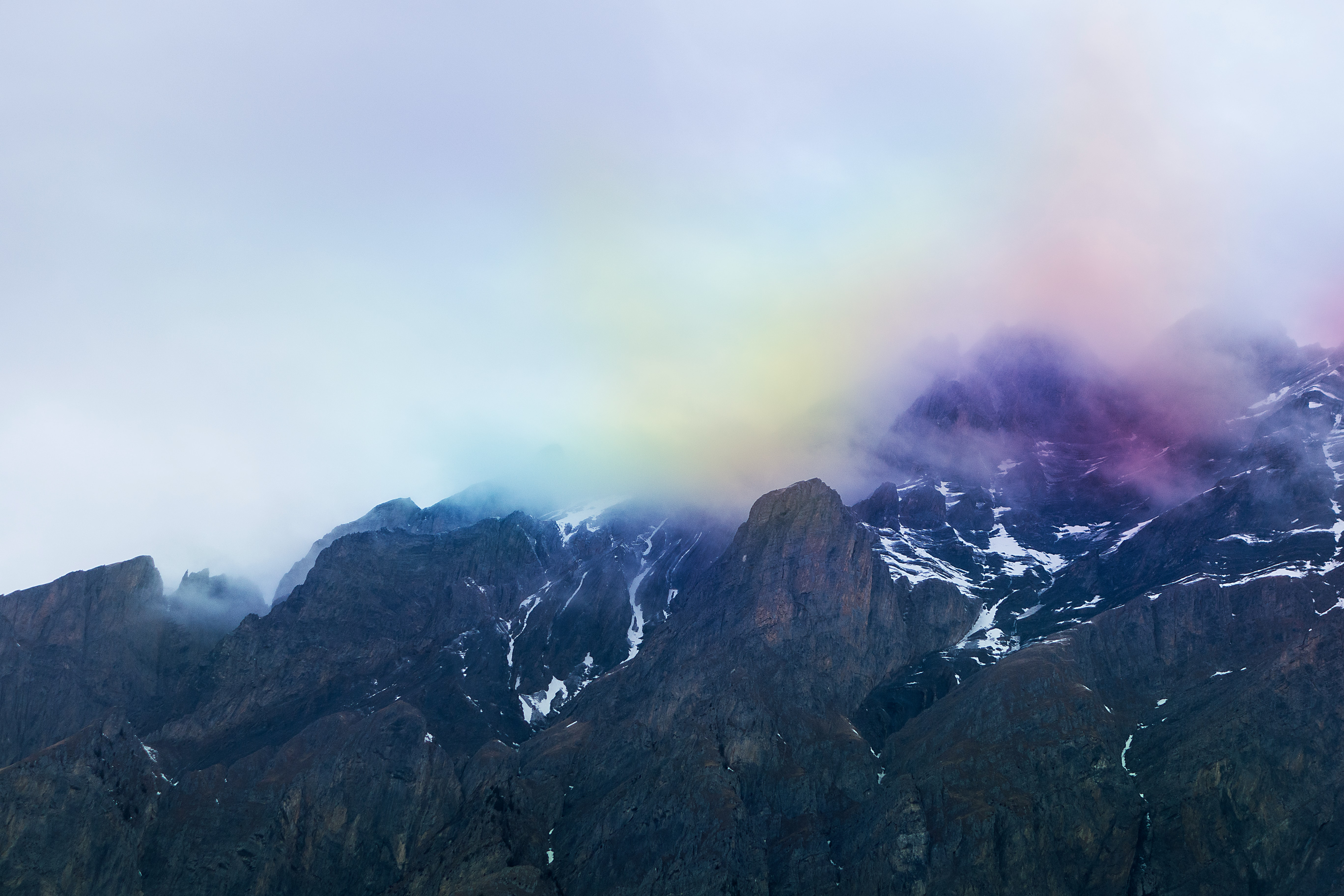 Rainbow colored smoke and clouds over dark mountains in Ovronnaz
