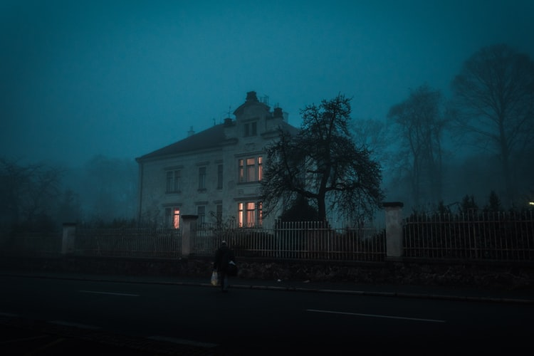 A creepy looking house that may be haunted. It's big, white, sitting in a foggy mist, with a few lights on at night.
