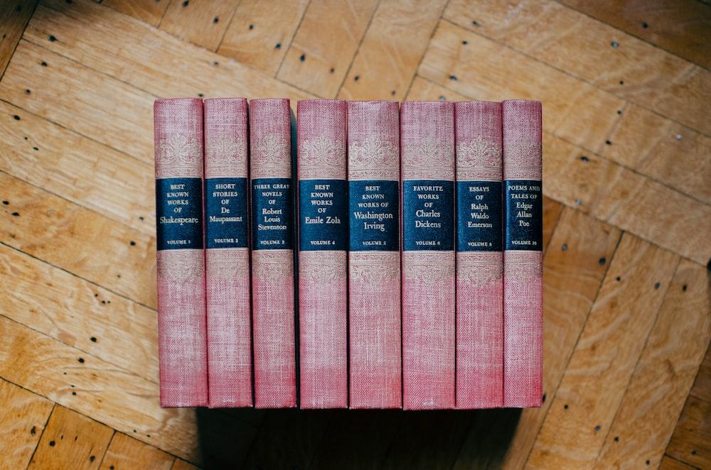 pile of red hardbound books on brown panel