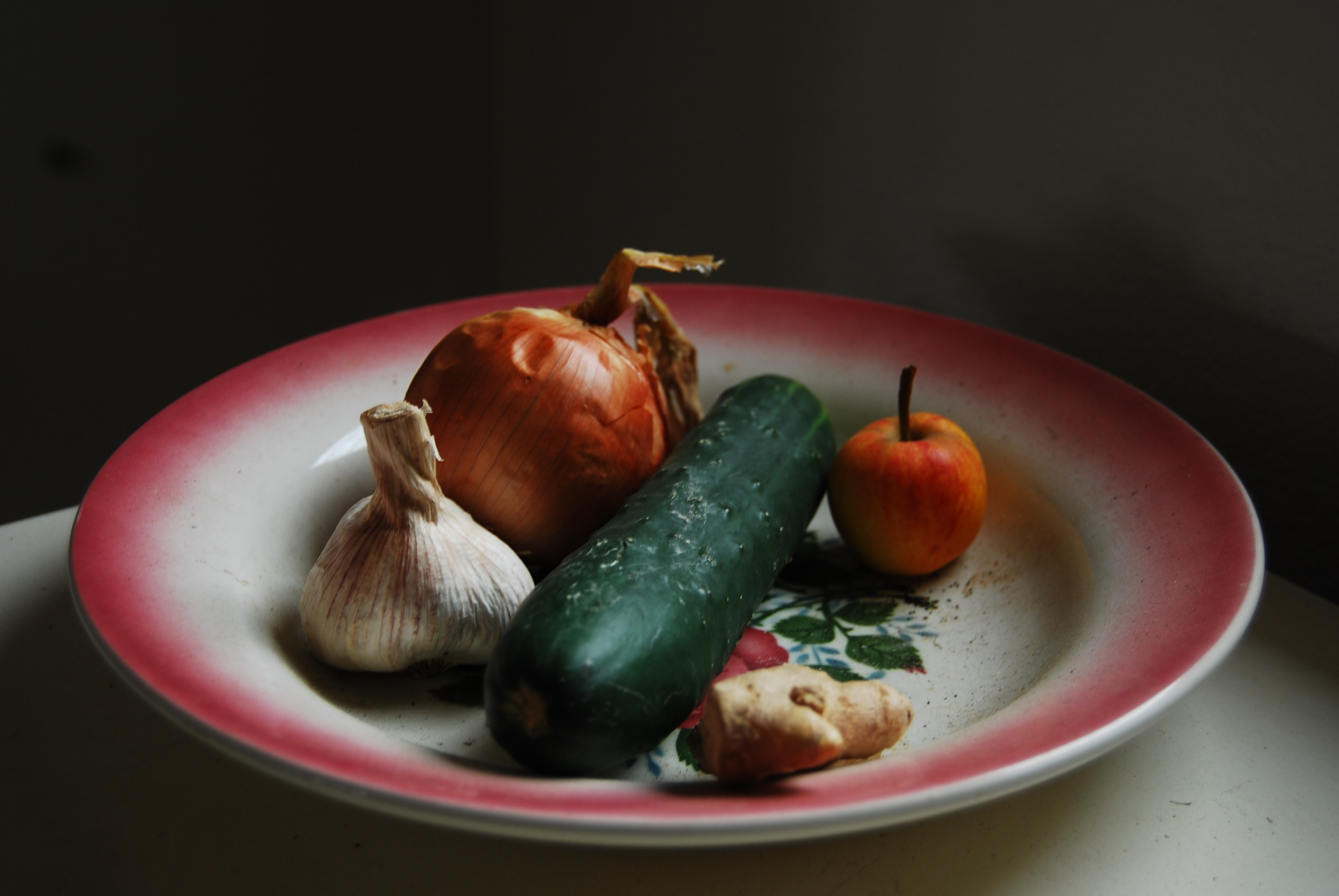 onion, garlic, ginger, and green vegetable on round white and red plate
