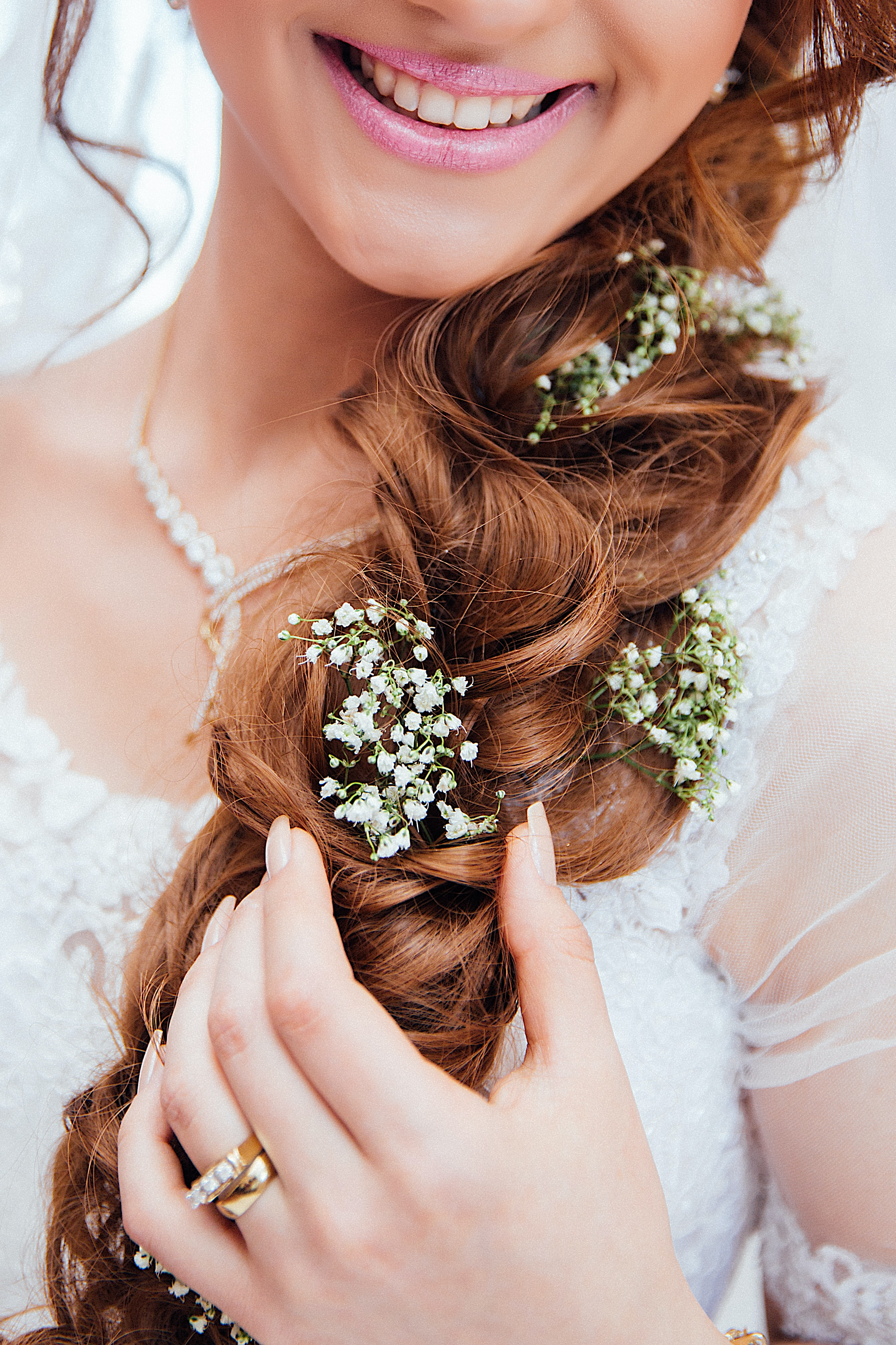 A smiling woman in a bridal dress with tiny white flowers in her plaited hair