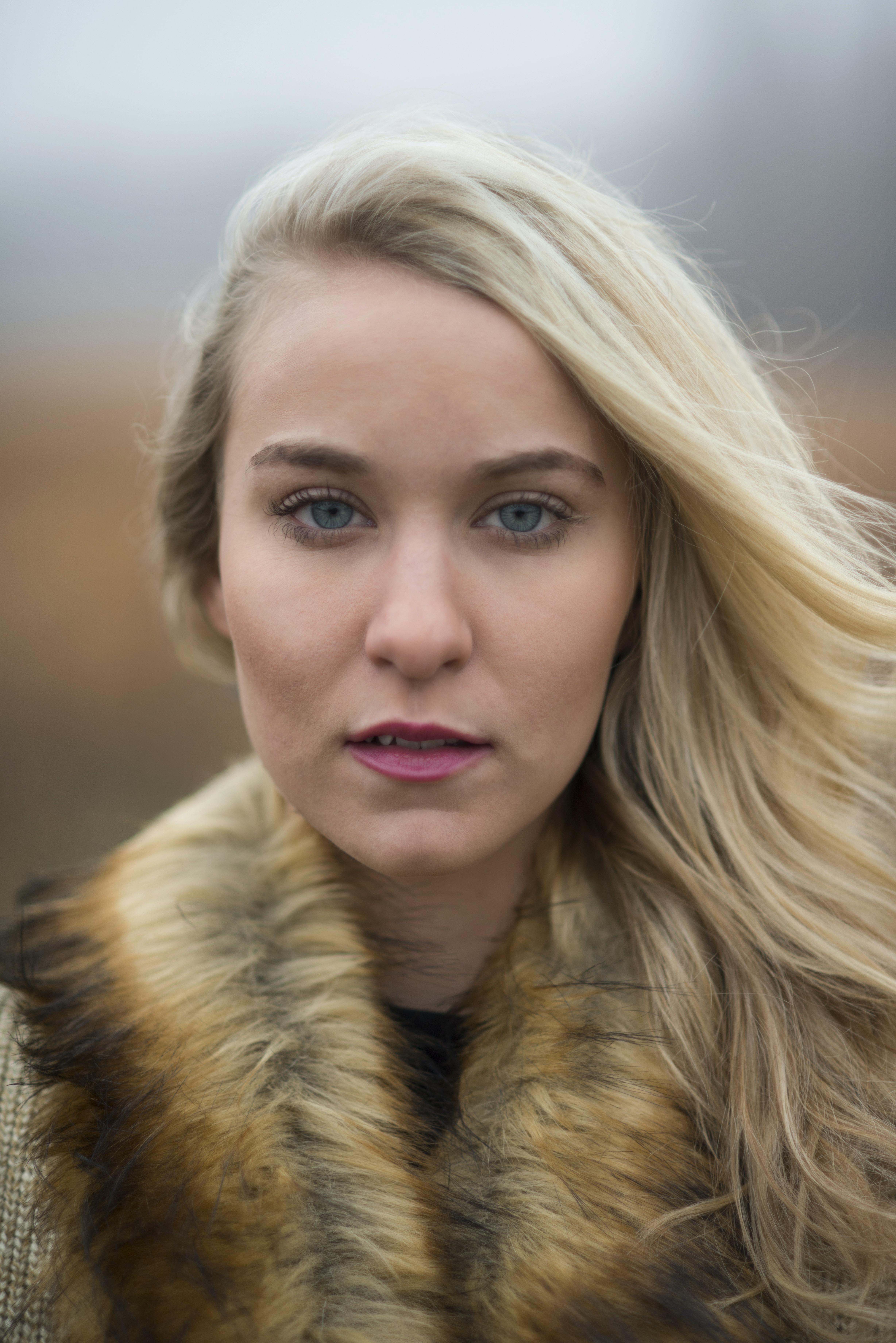 woman looking at camera wearing brown fur scarf