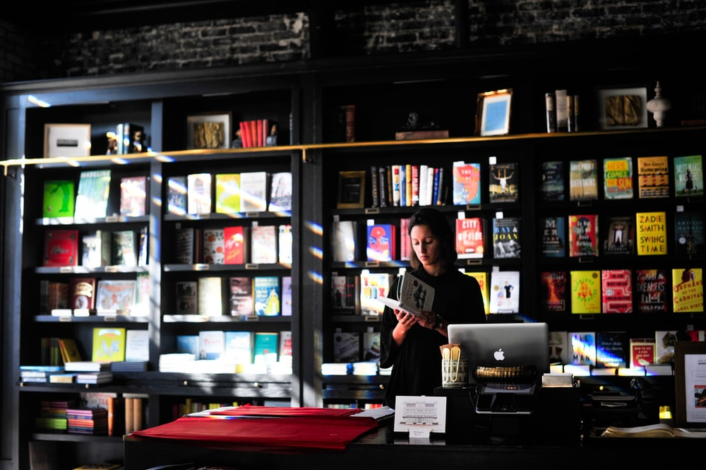 woman standing in front of book shelf
