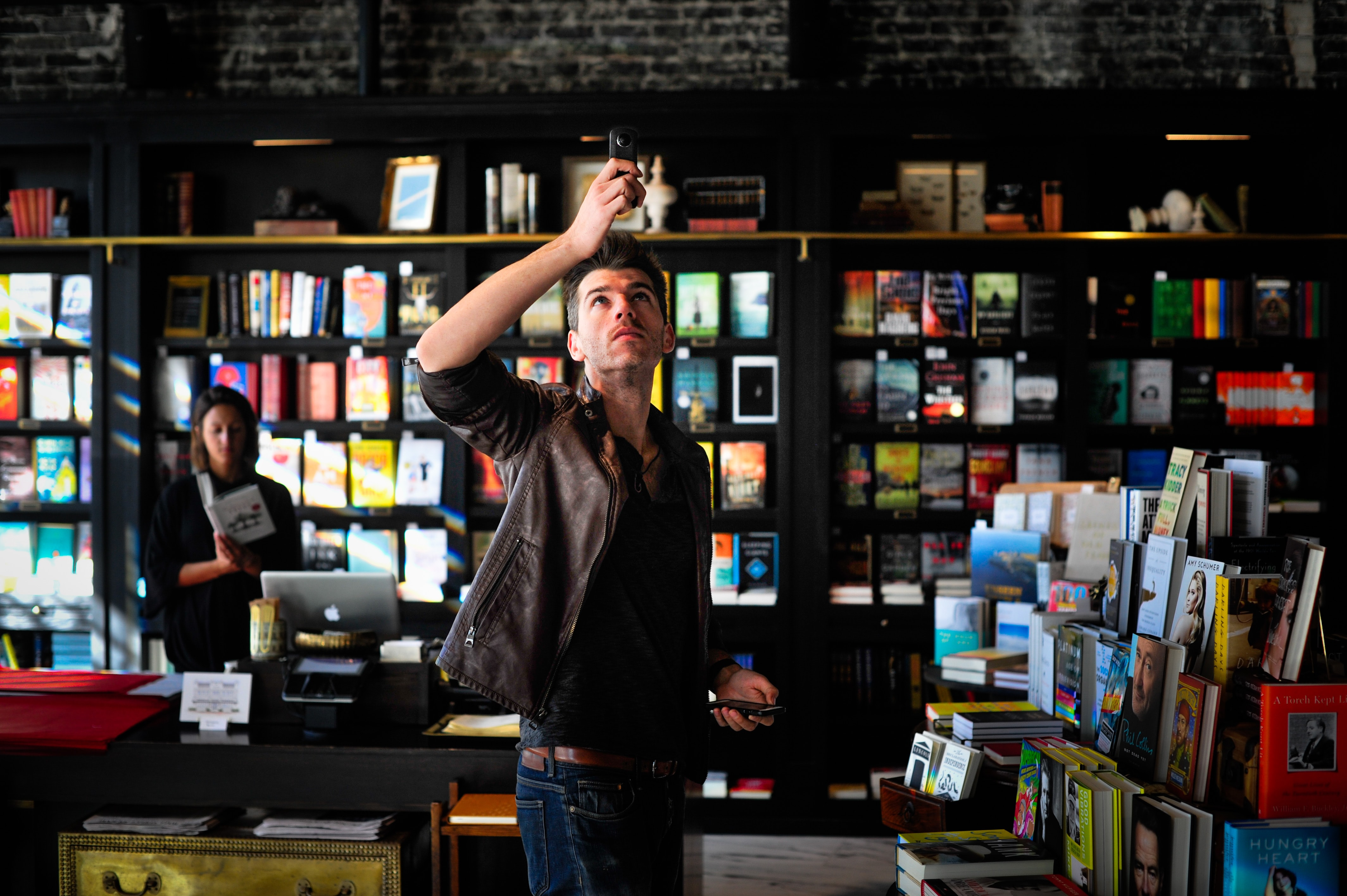 A man in a leather jacket lifting up an electronic device in a bookshop
