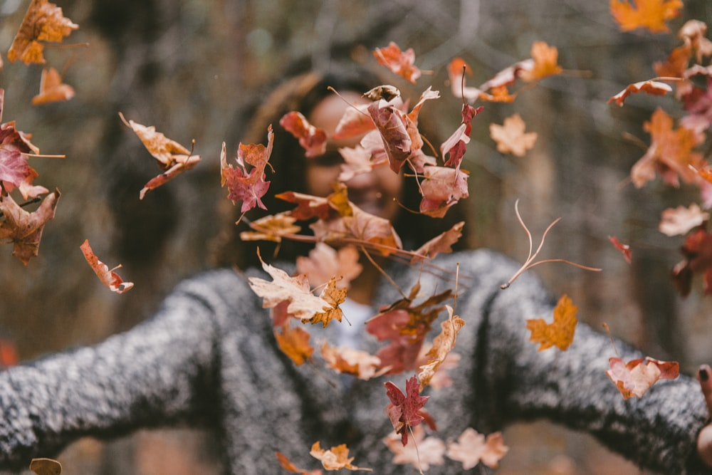 woman throwing maple leaves