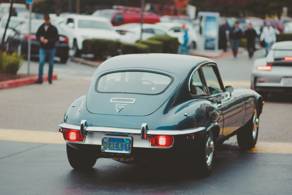 teal coupe passing by in street