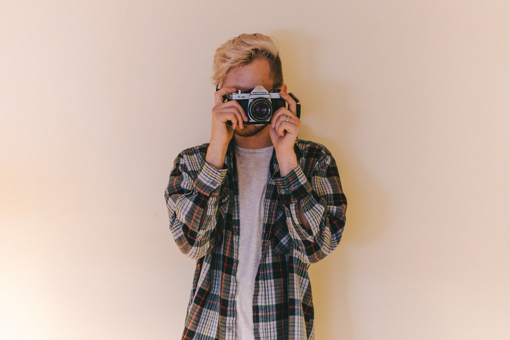 man wearing black, gray, and brown plaid collared button-up long-sleeved shirt standing while using camera