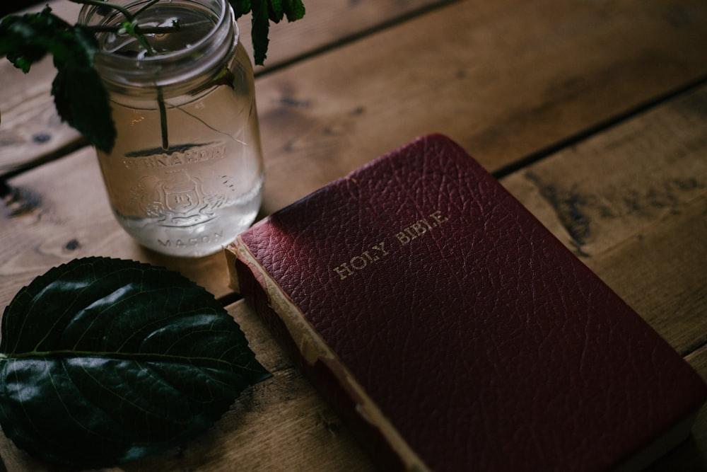 Holy Bible beside clear mason jar on table