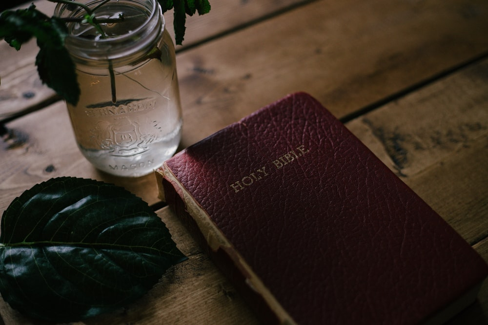 Holy Bible beside clear mason jar on table