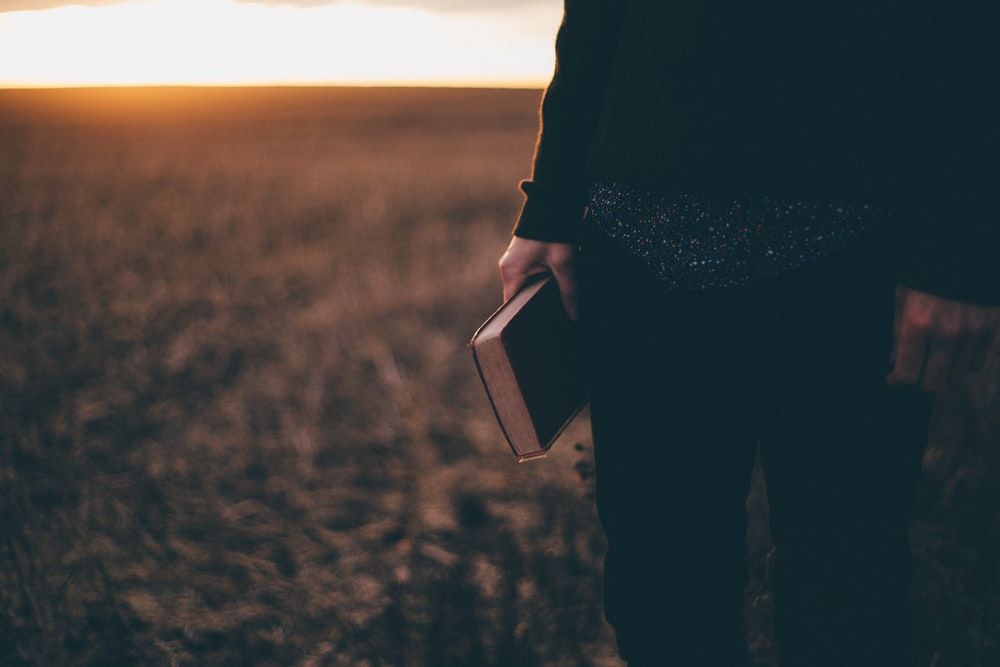person holding book while standing on field