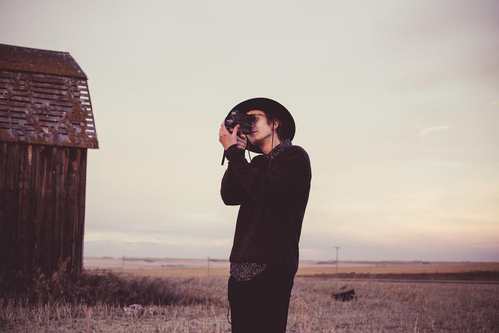man holding camera near barn house