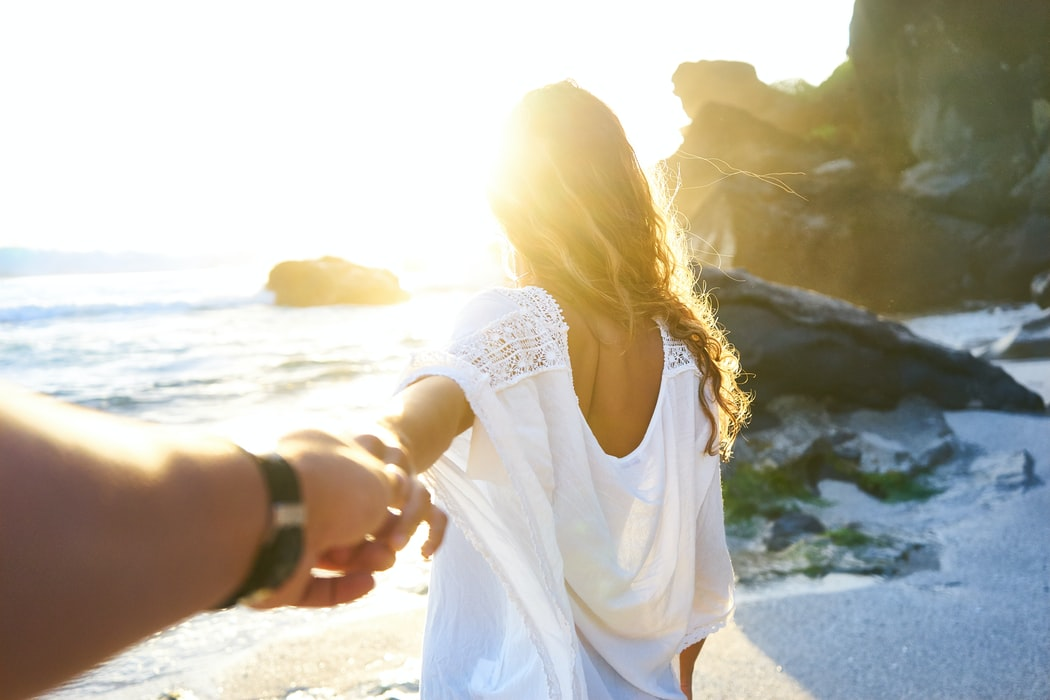 man following woman into sunset on beach
