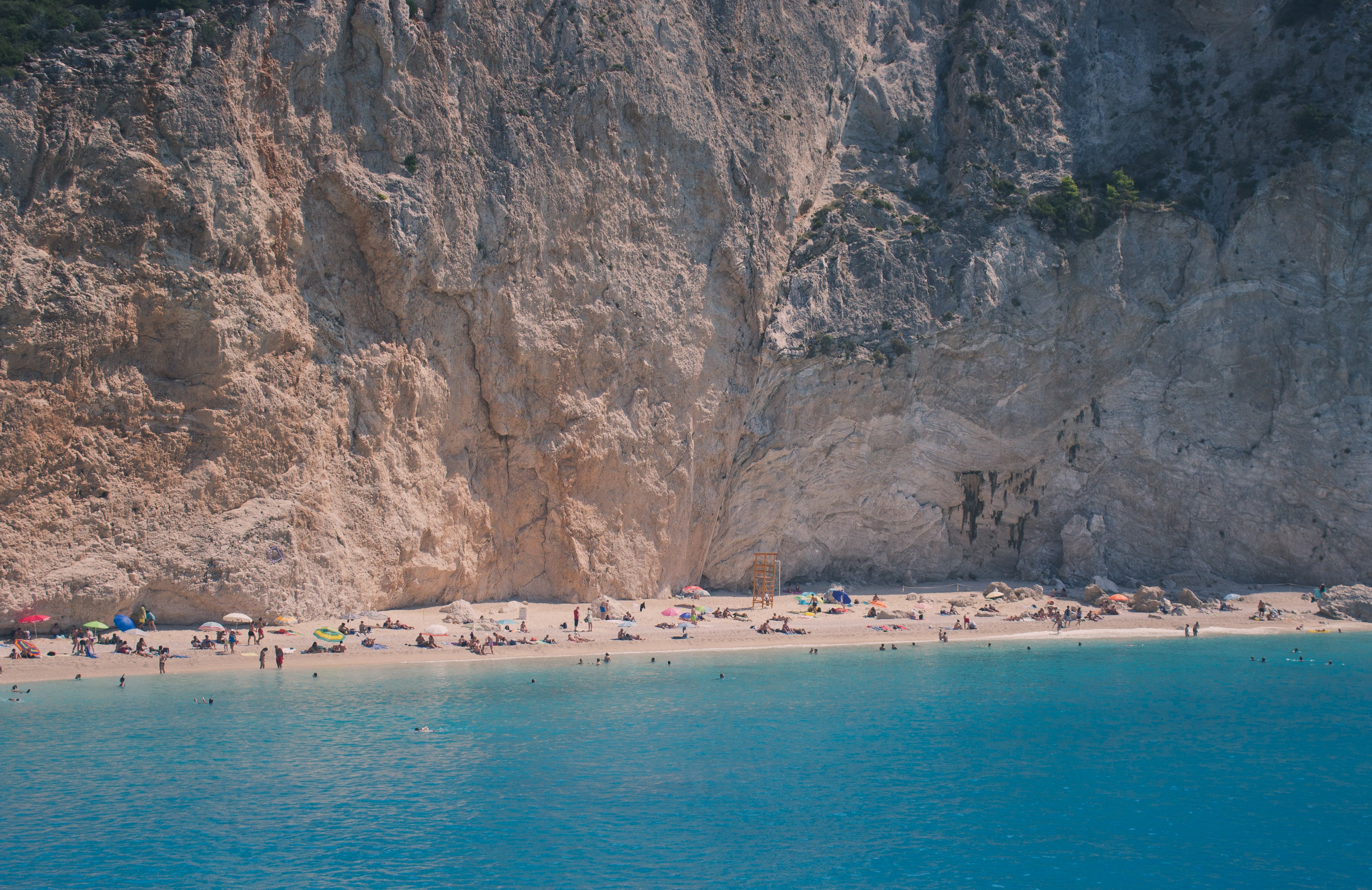 Tourists vacationing on a golden beach with a steep rock face at the back